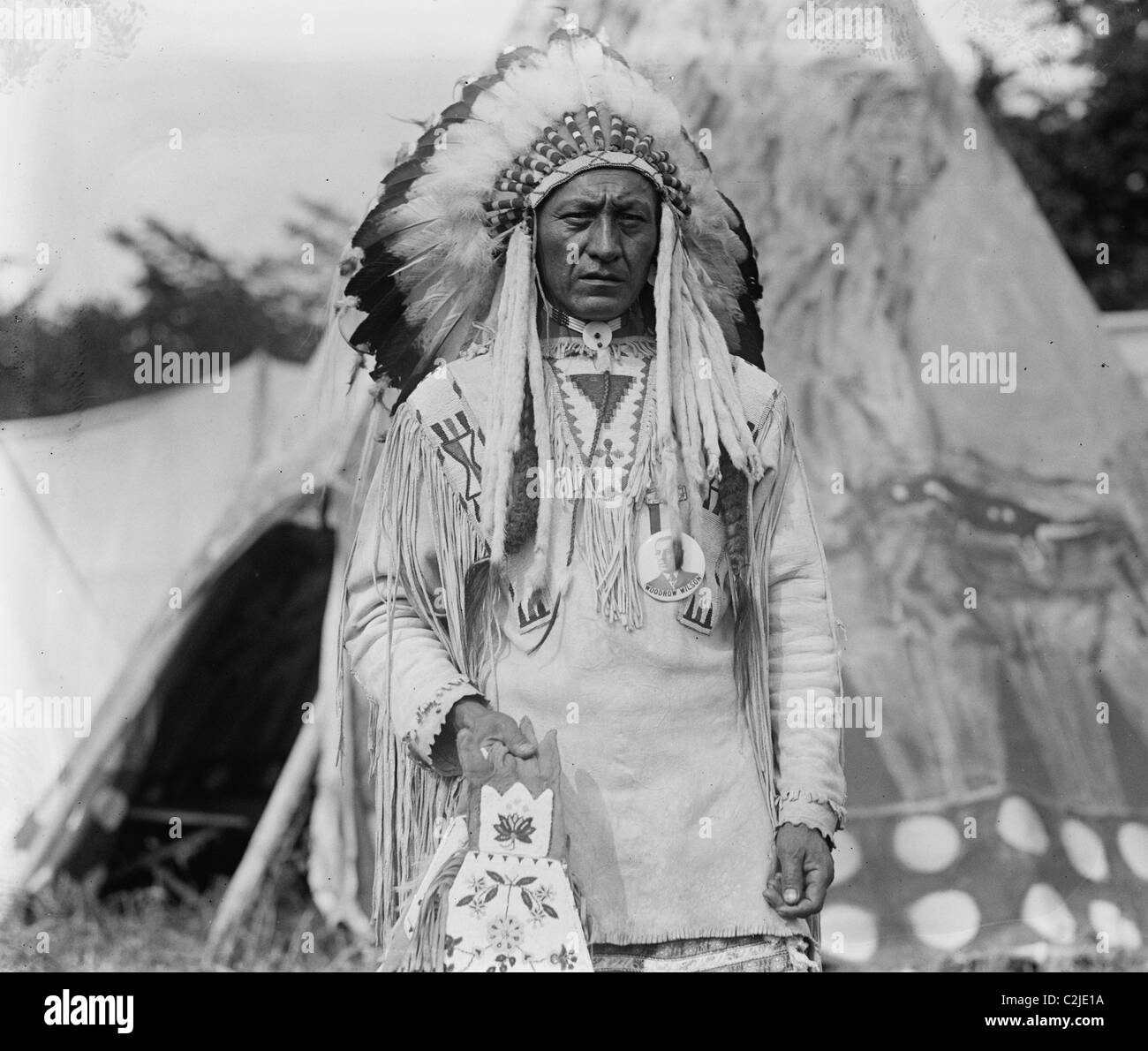 Native American Chief in Traditional Clothing and Feathered Bonnet - Stock Image