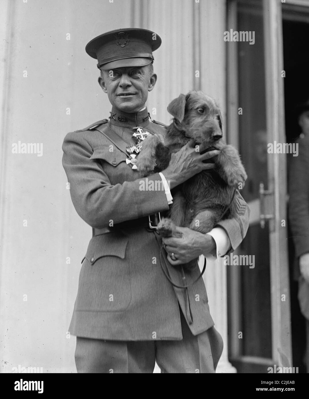 Highly Decorated WWI Marine Corps Colonel Holds a dog endearingly - Stock Image