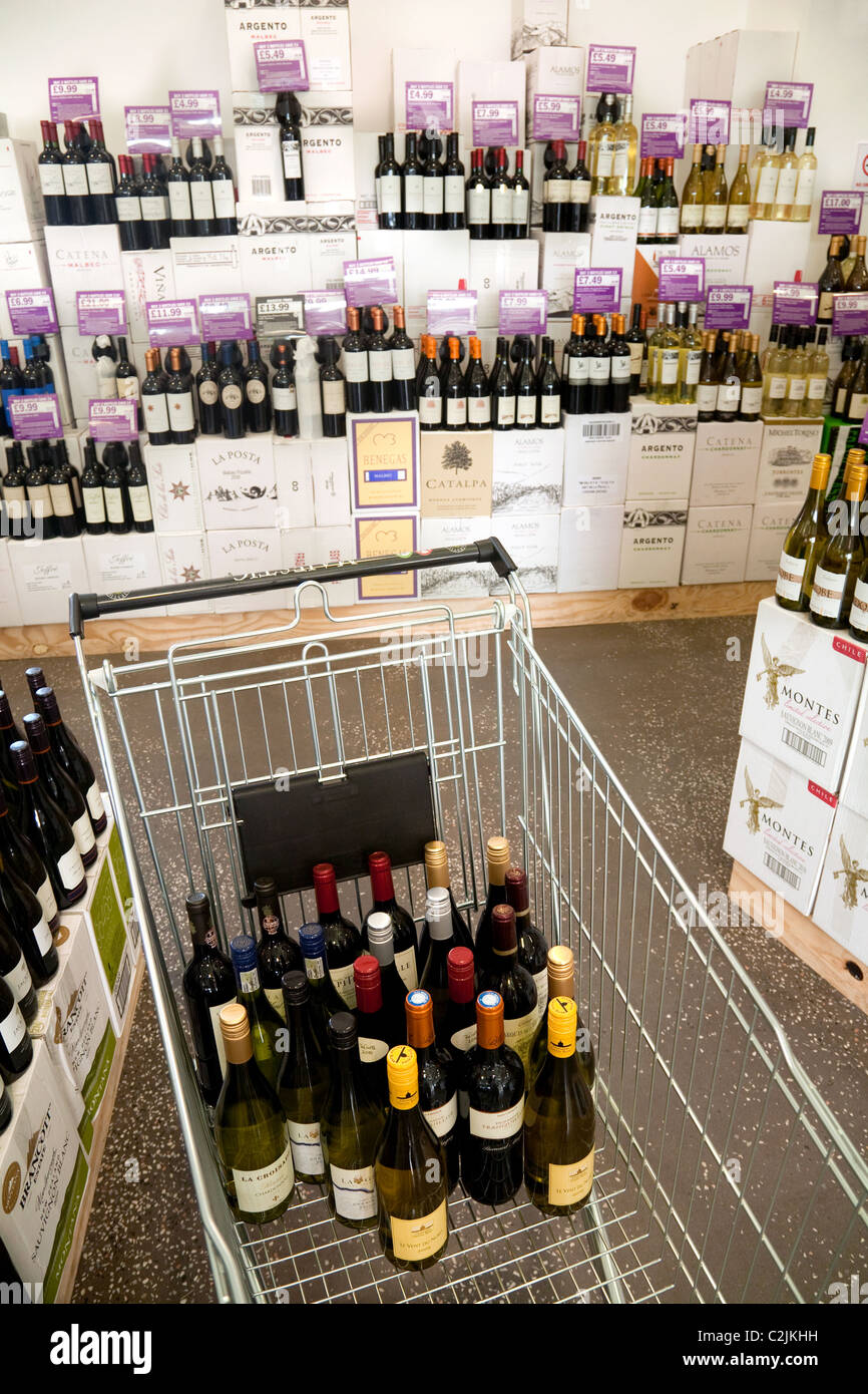 Shopping trolley full of wine in a wine store,  UK - Stock Image