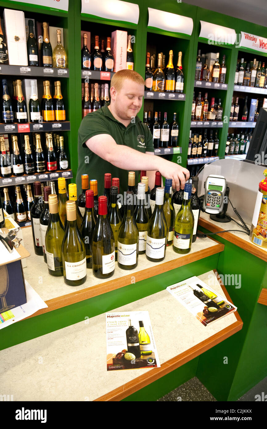 Friendly staff at the Majestic Wine store price up bottles of wine bought, Newmarket Suffolk UK Stock Photo