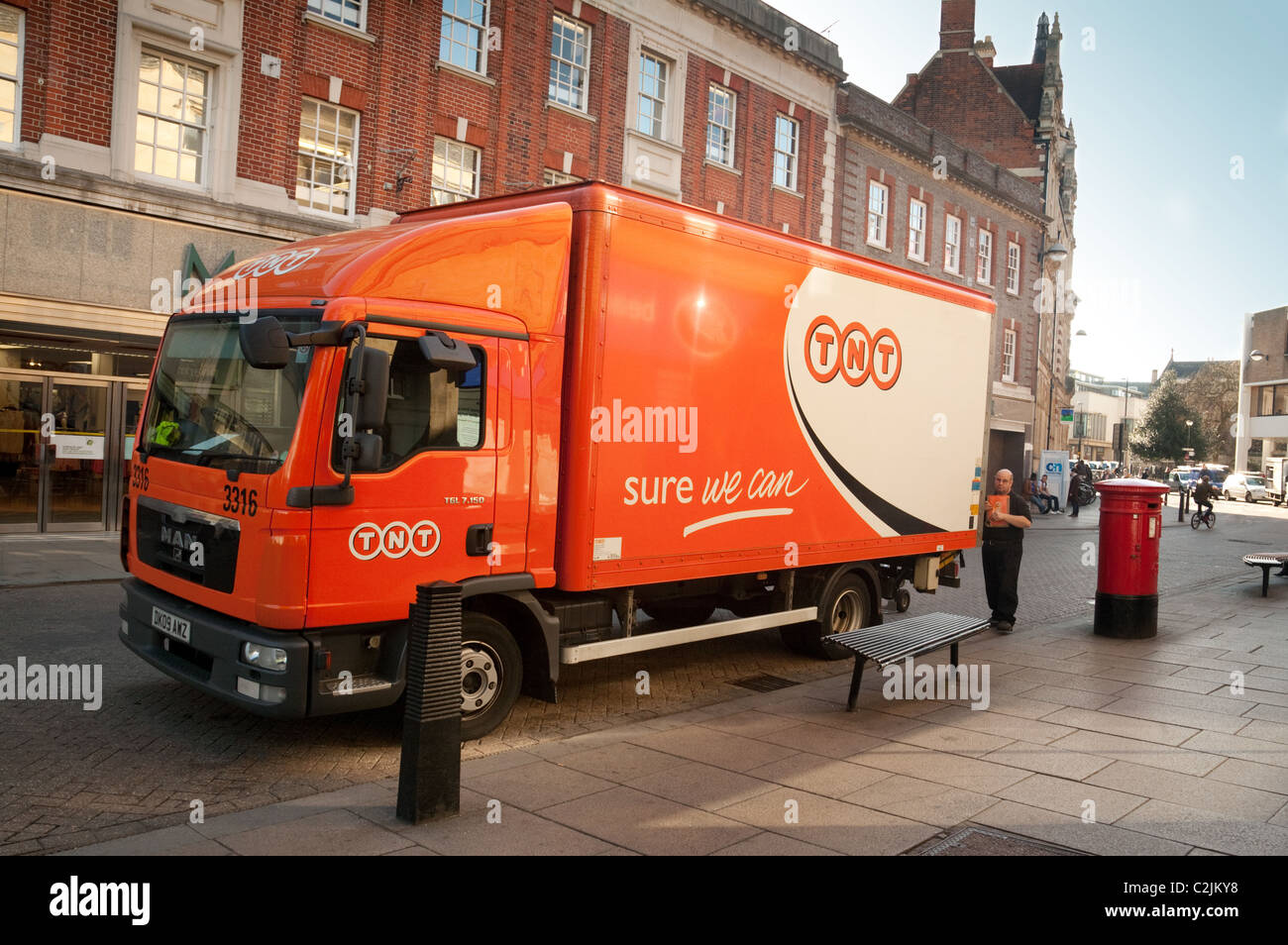 A TNT postman and his delivery truck at a postbox, Sidney Street Cambridge UK - Stock Image