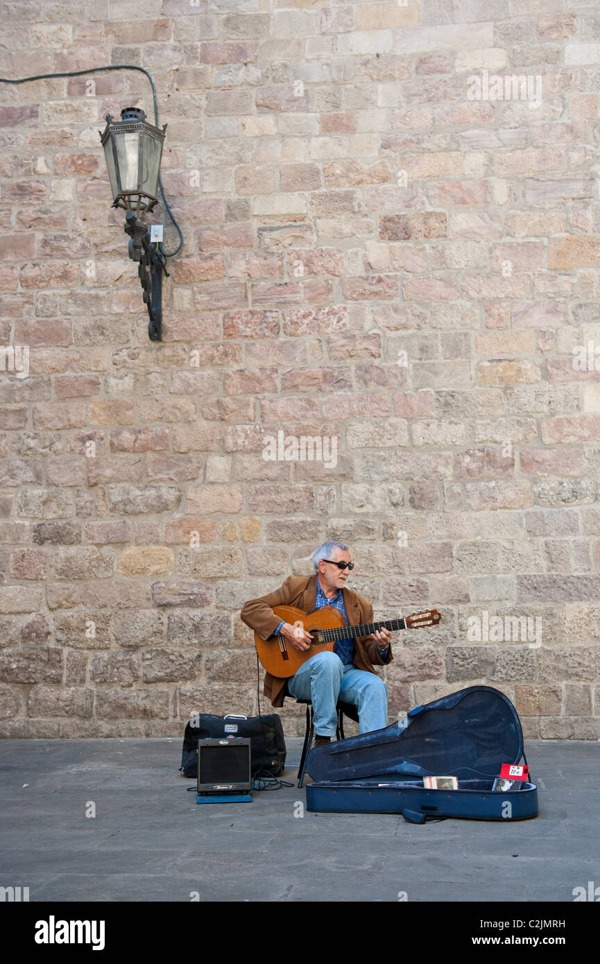 Spanish guitar player performing in the street of the Gothic area of Barcelona, Spain - Stock Image