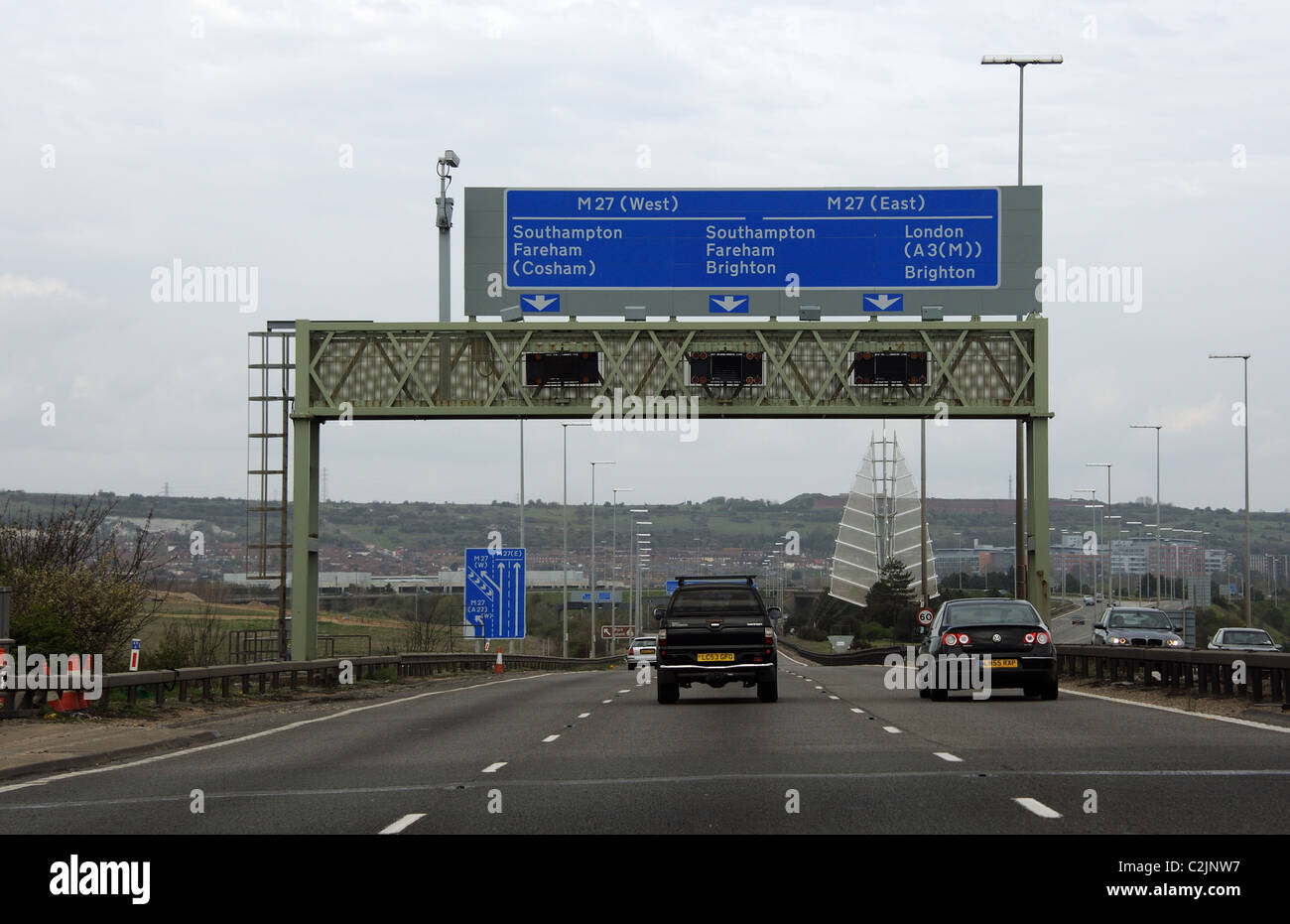 Traffic exiting Portsmouth southern England passing road signs for the M27 motorways east and west - Stock Image