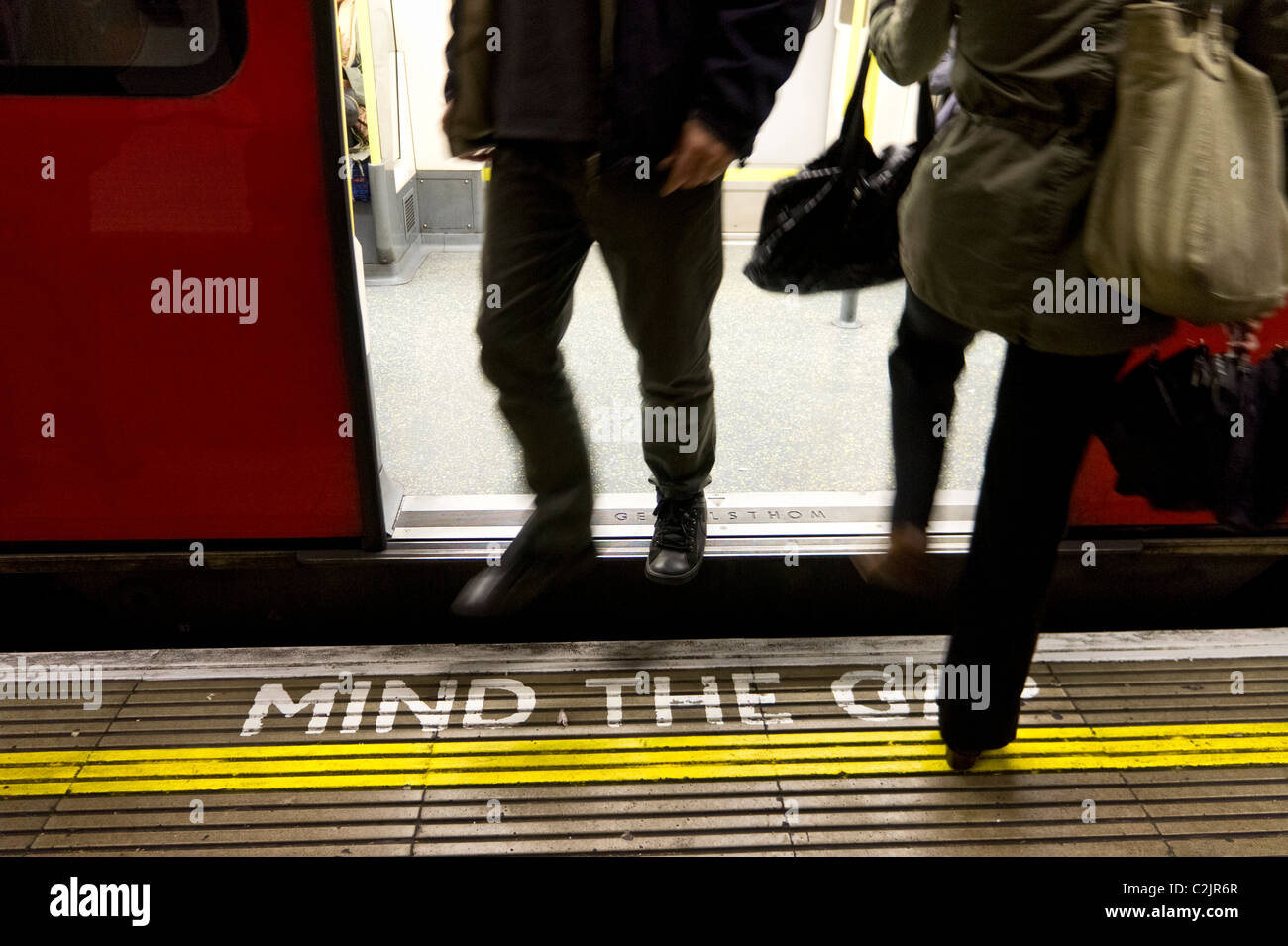 People exit and enter a London Underground tube train over a