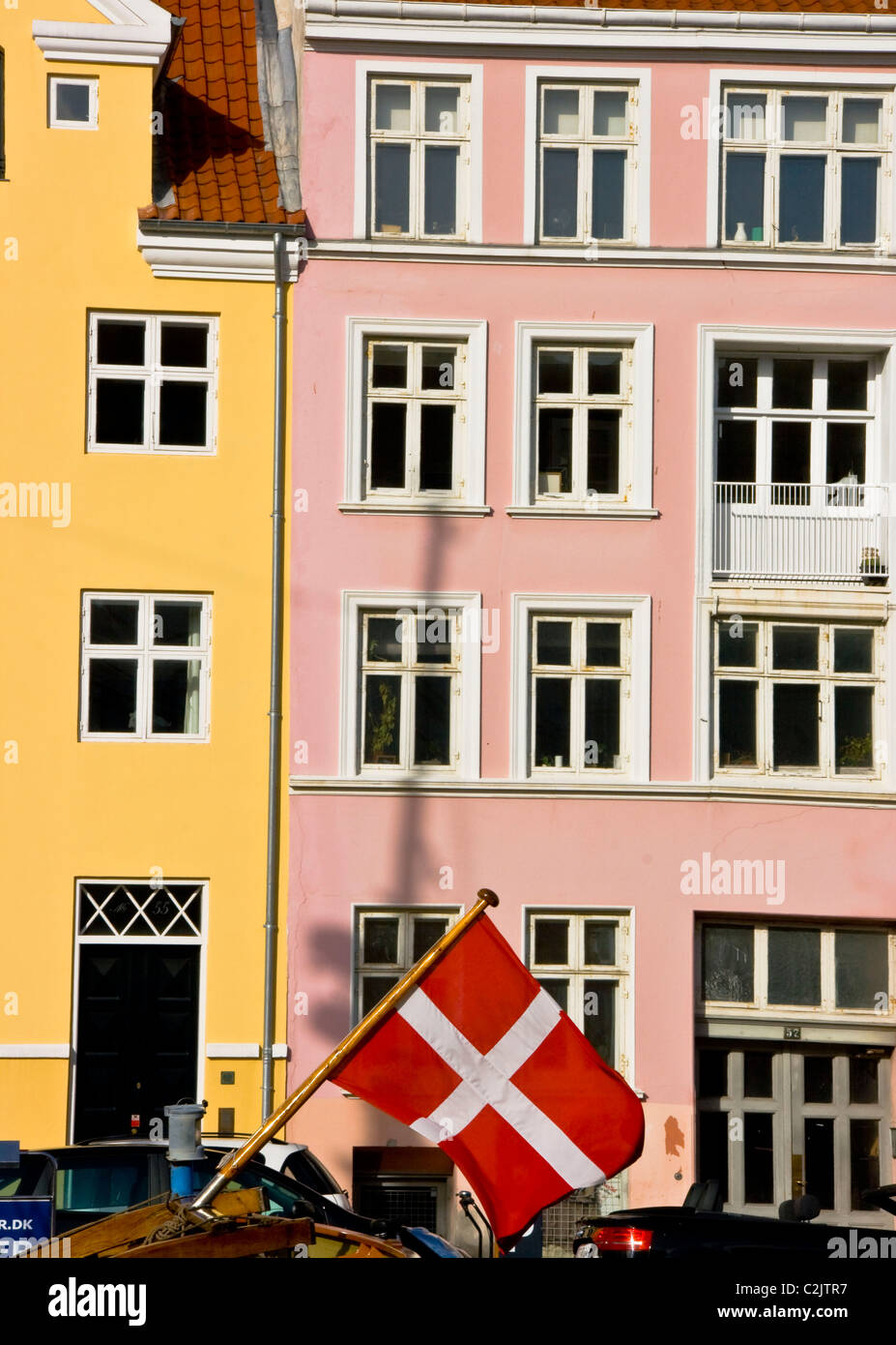 Danish flag flying and waterfront houses in Nyhavn (New harbor) Copenhagen Denmark Europe - Stock Image