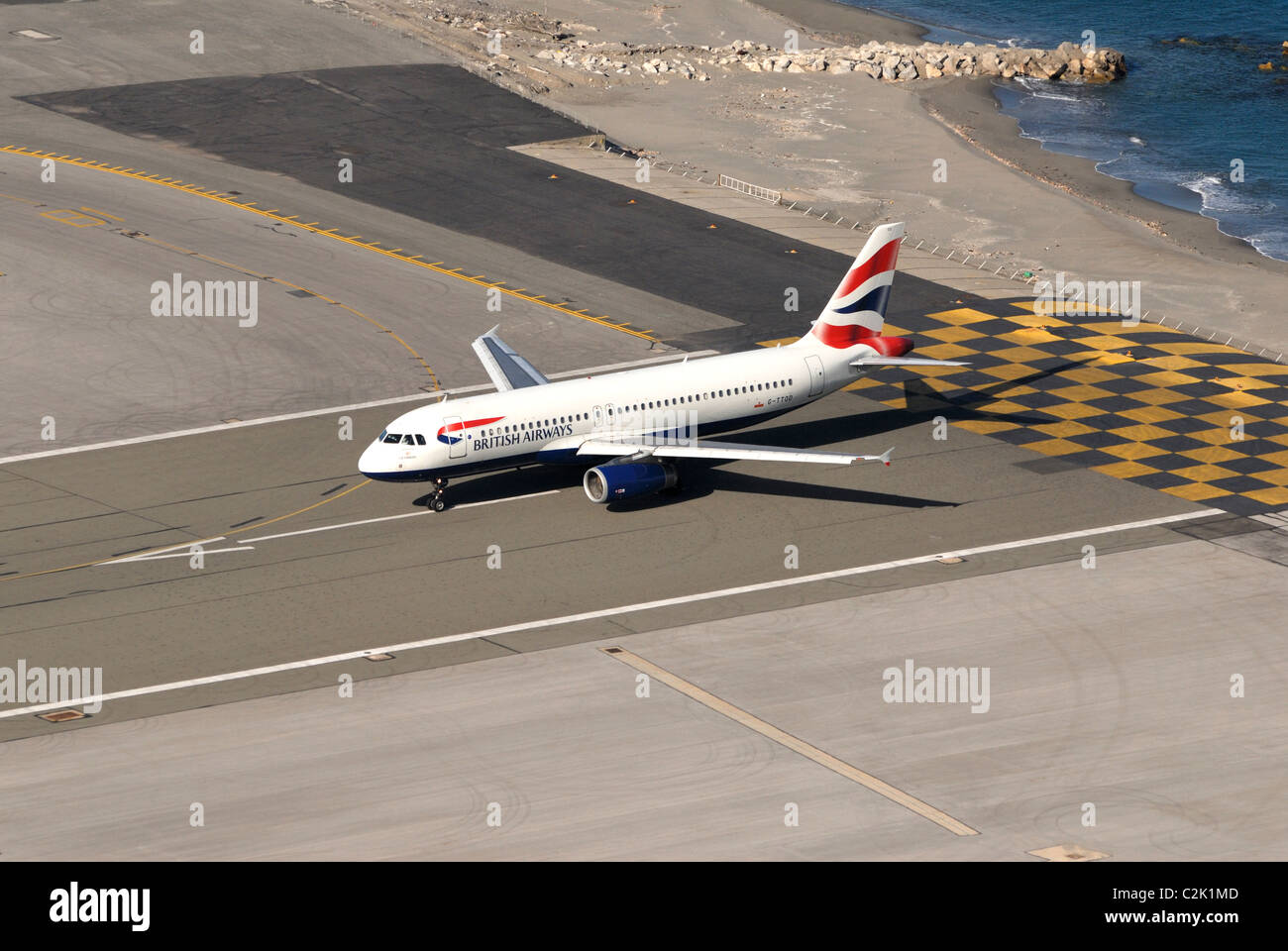 British Airways twin engined jet waiting to take off at the end of Gibraltars runway - Stock Image