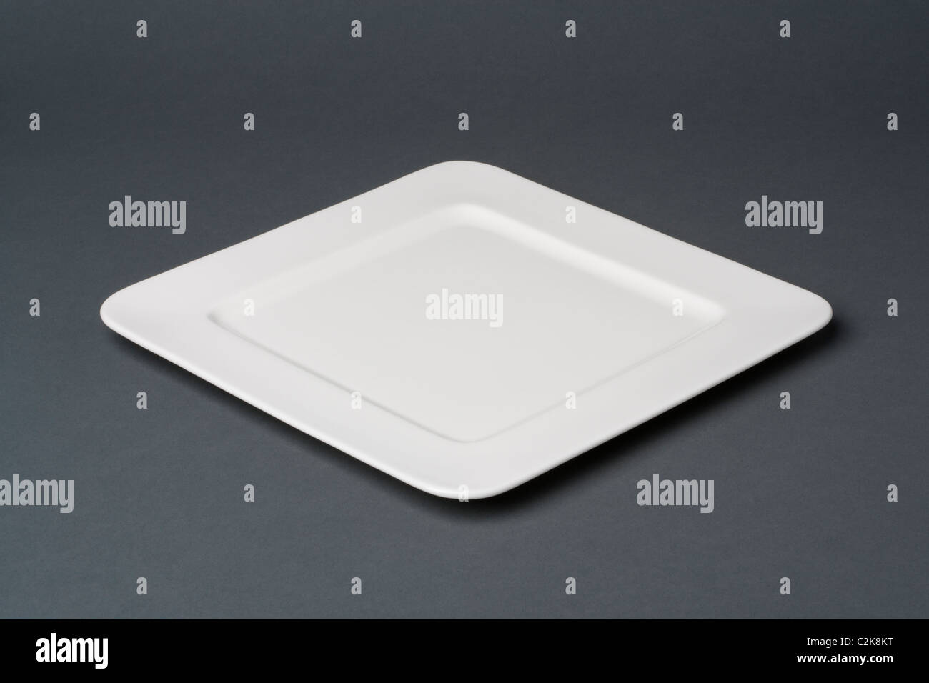 Square white dinner plate on a grey background - Stock Image