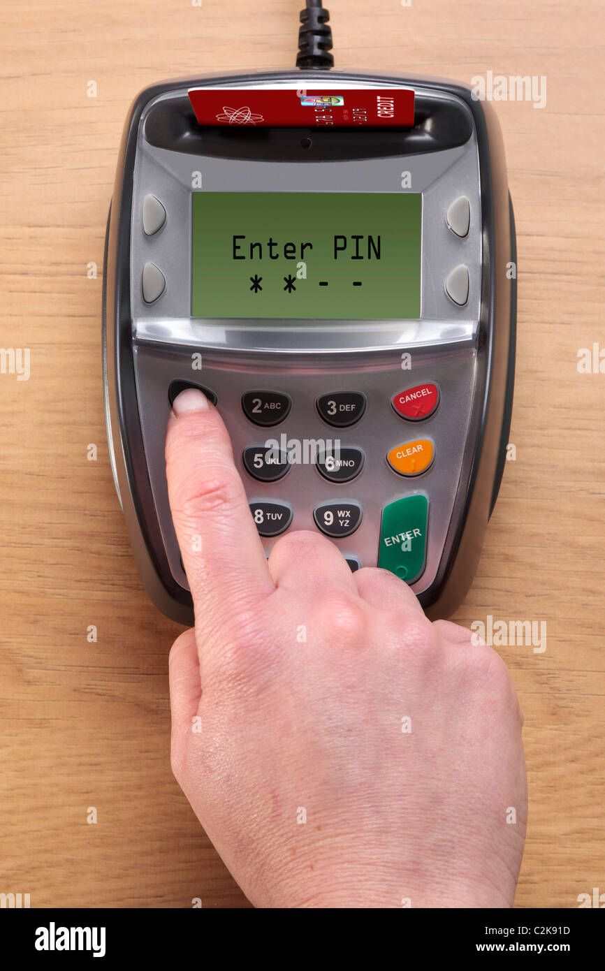 Photo of a womans hand typing her number into a Chip and Pin credit card terminal, the card in the machine is a - Stock Image
