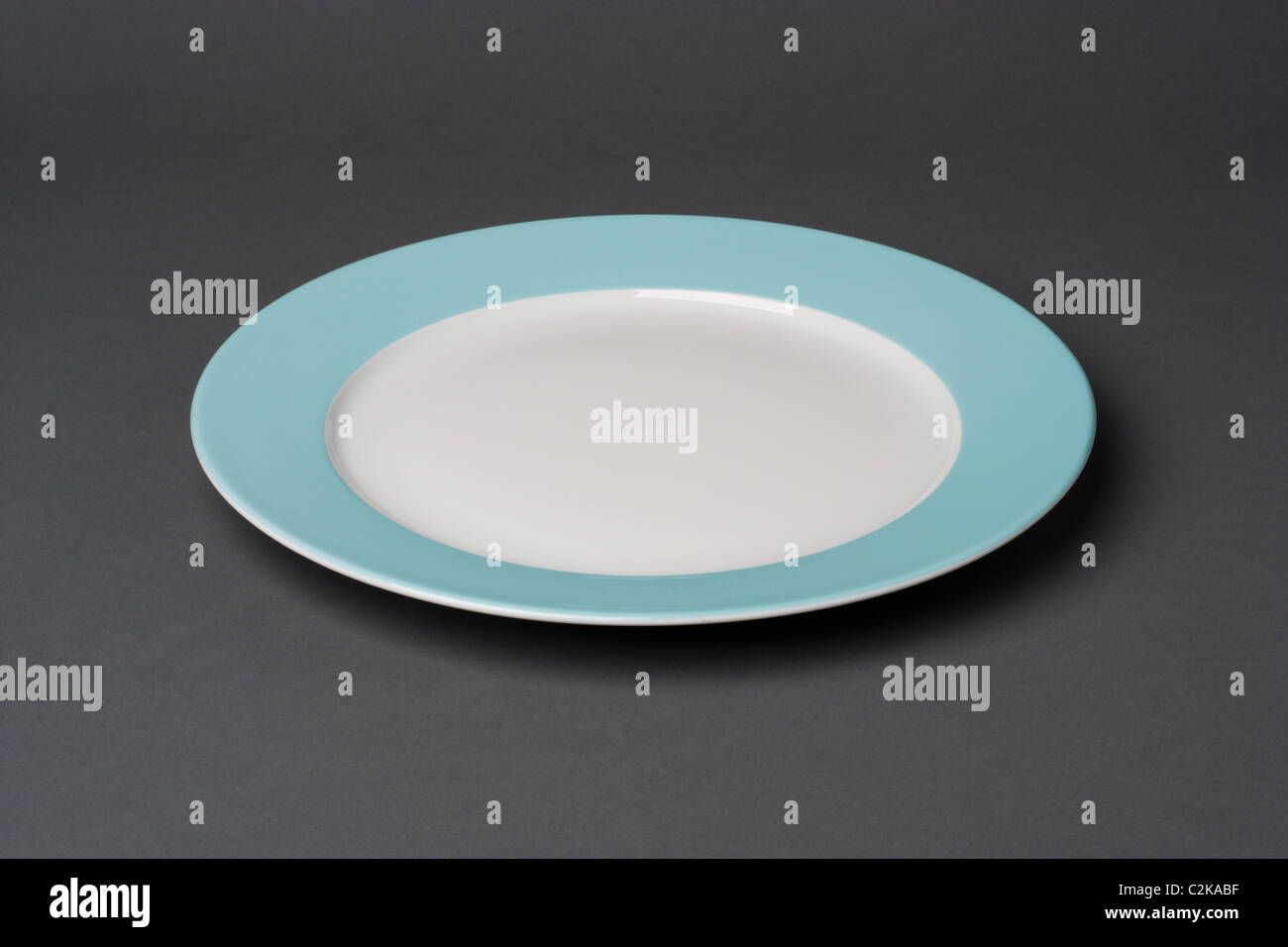 blue dinner plate on a grey background - Stock Image
