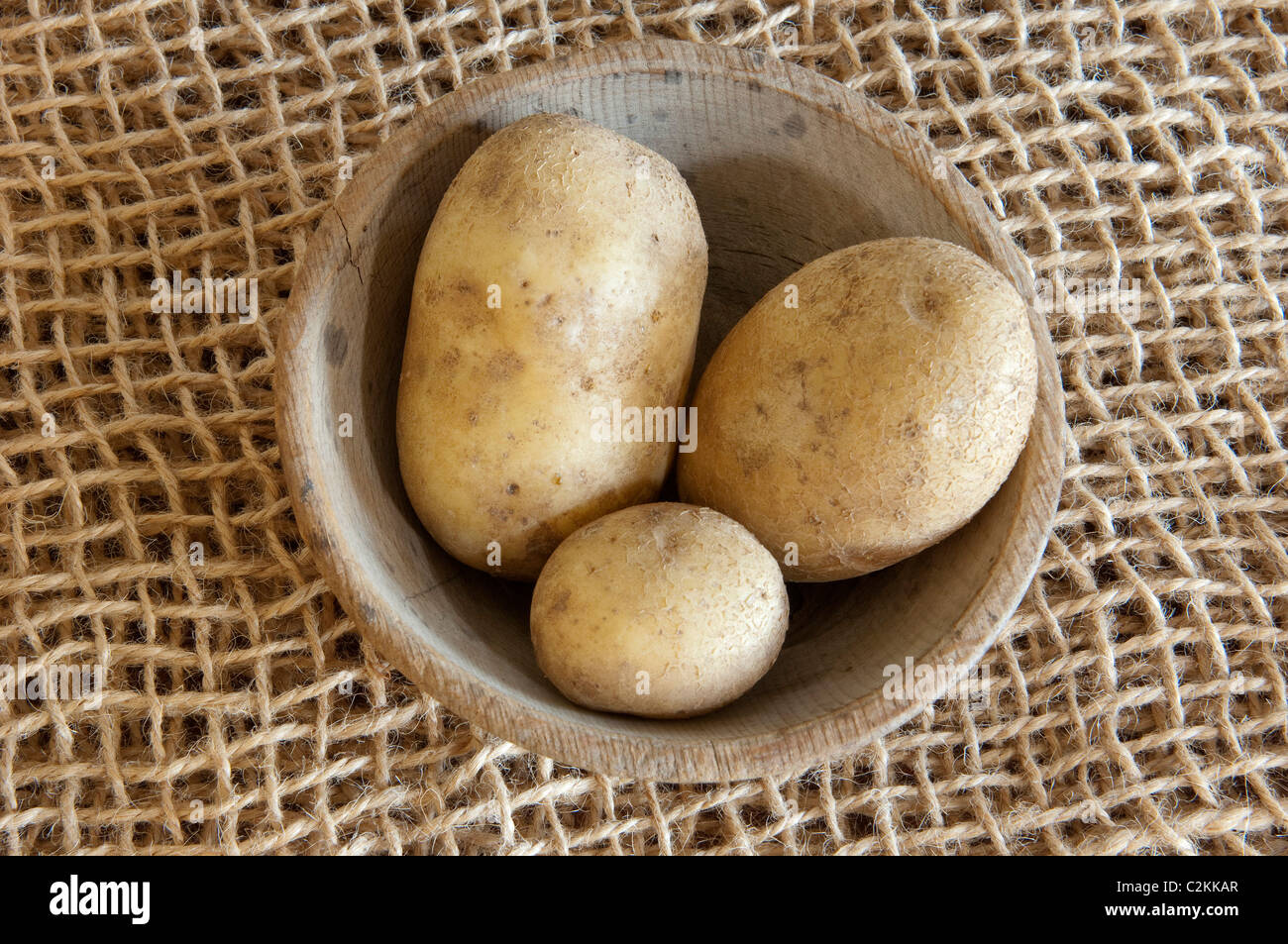 Up To Date Potato (Solanum tuberosum Up To Date). Potatoes in a wooden bowl. - Stock Image