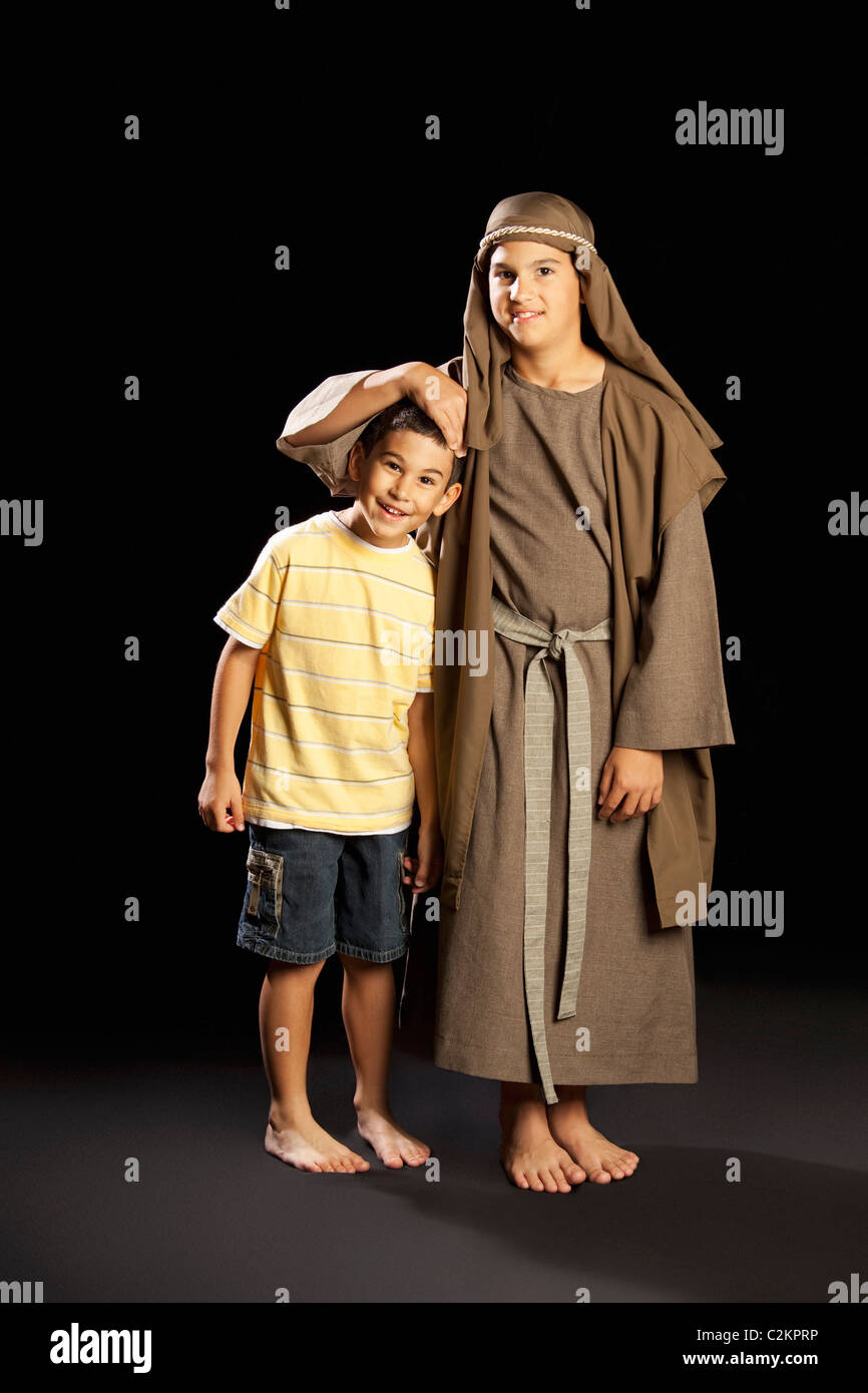 A Young Boy Dressed Up As Jesus Embracing Another Boy - Stock Image