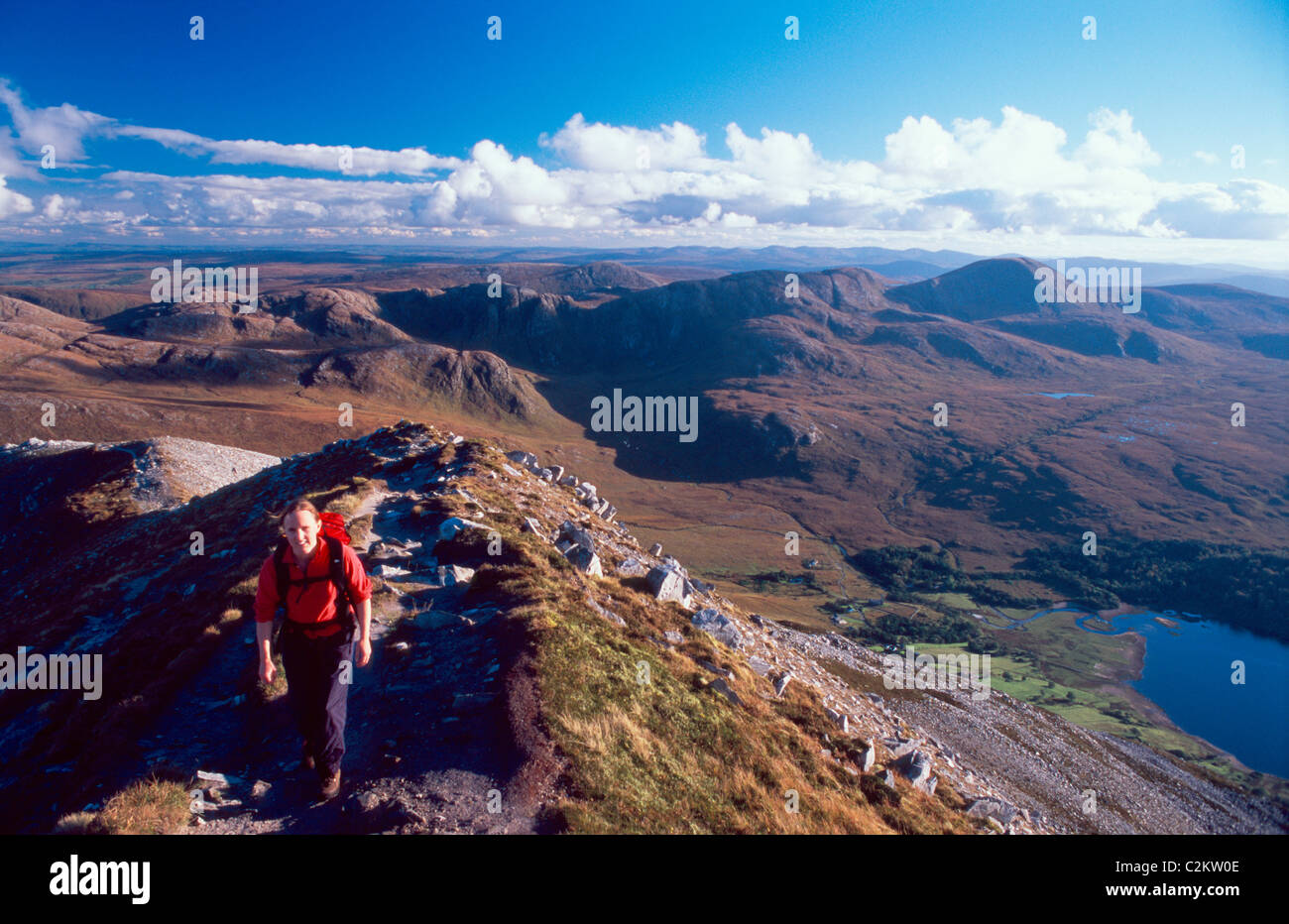 Walker on the summit ridge of Errigal Mountain, with the Derryveagh Mountains behind. County Donegal, Ireland. - Stock Image
