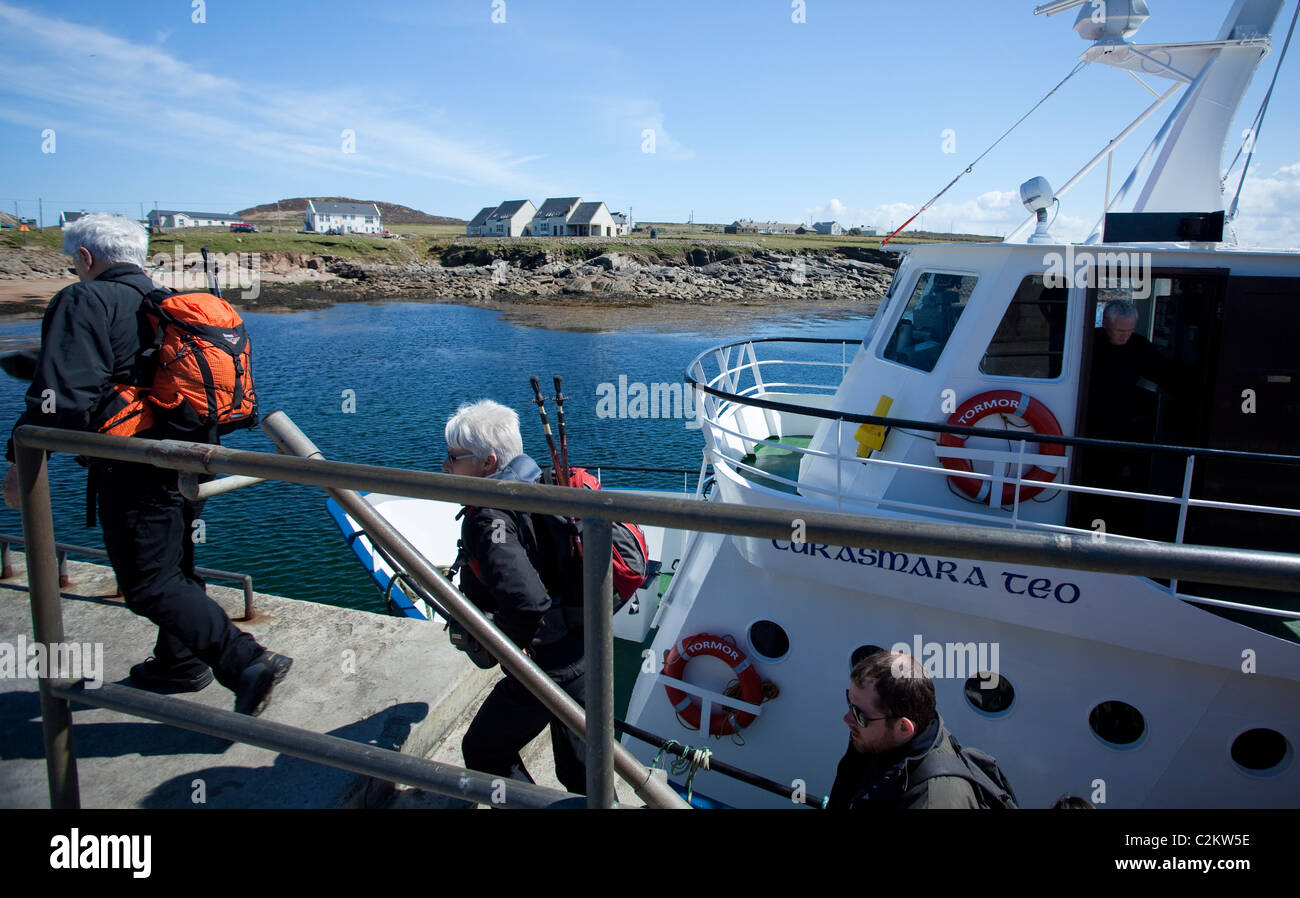 Tourists disembarking the ferry at Tory Island, County Donegal, Ireland. - Stock Image