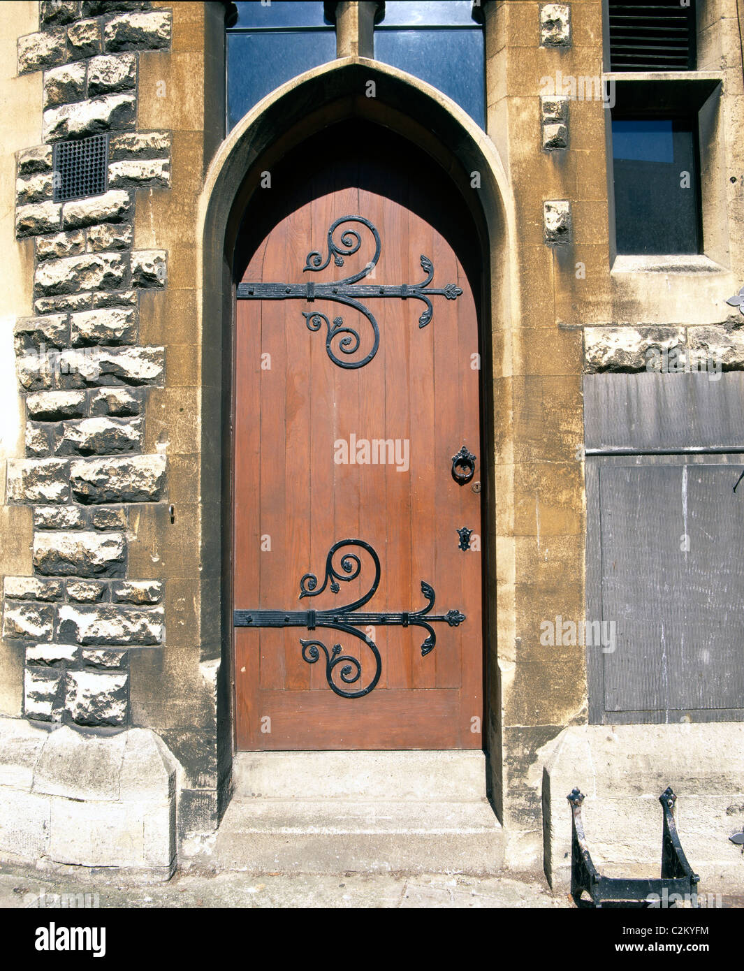 Doors - ecclesiastical type door with ornate ironmongery / hinged in rough cast stone building - Stock Image