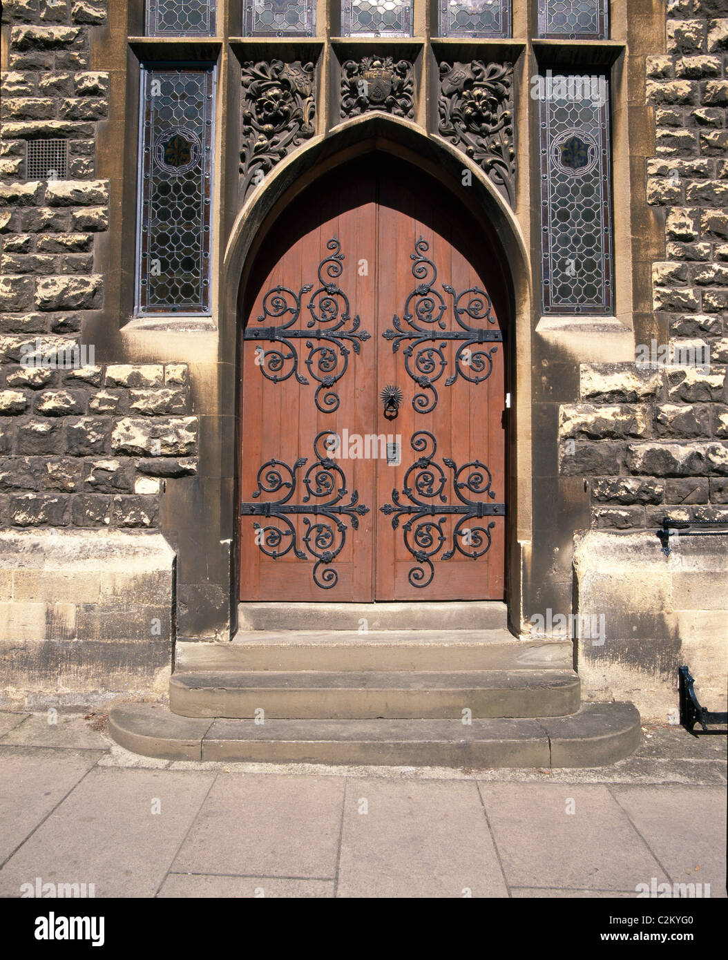 Doors -ecclesiastical type door with ornate ironmongery / hinged in rough cast stone building - Stock Image