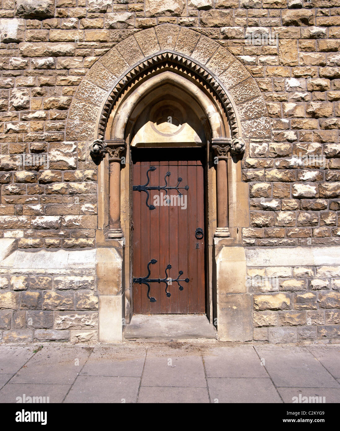 Doors - -ecclesiastical type door with ornate ironmongery / hinged in rough cast stone building - Stock Image