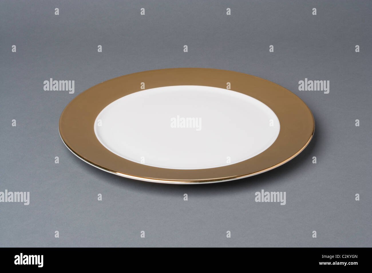 gold and white china crockery on a grey background - Stock Image