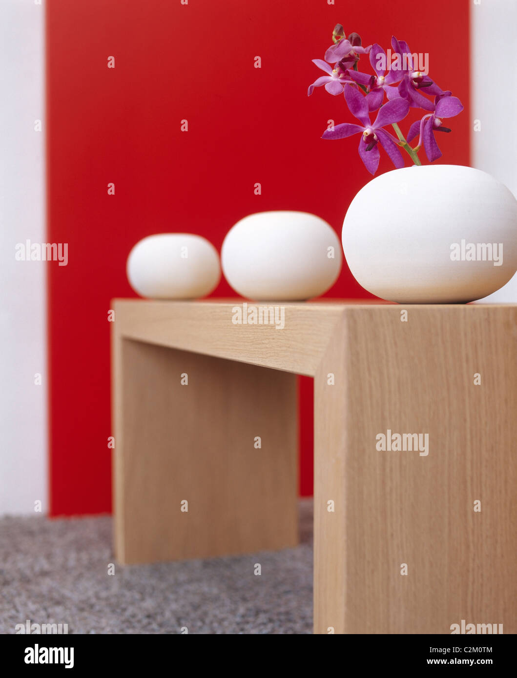 Contemporary Red Interior with Wooden Table and White Vases. - Stock Image