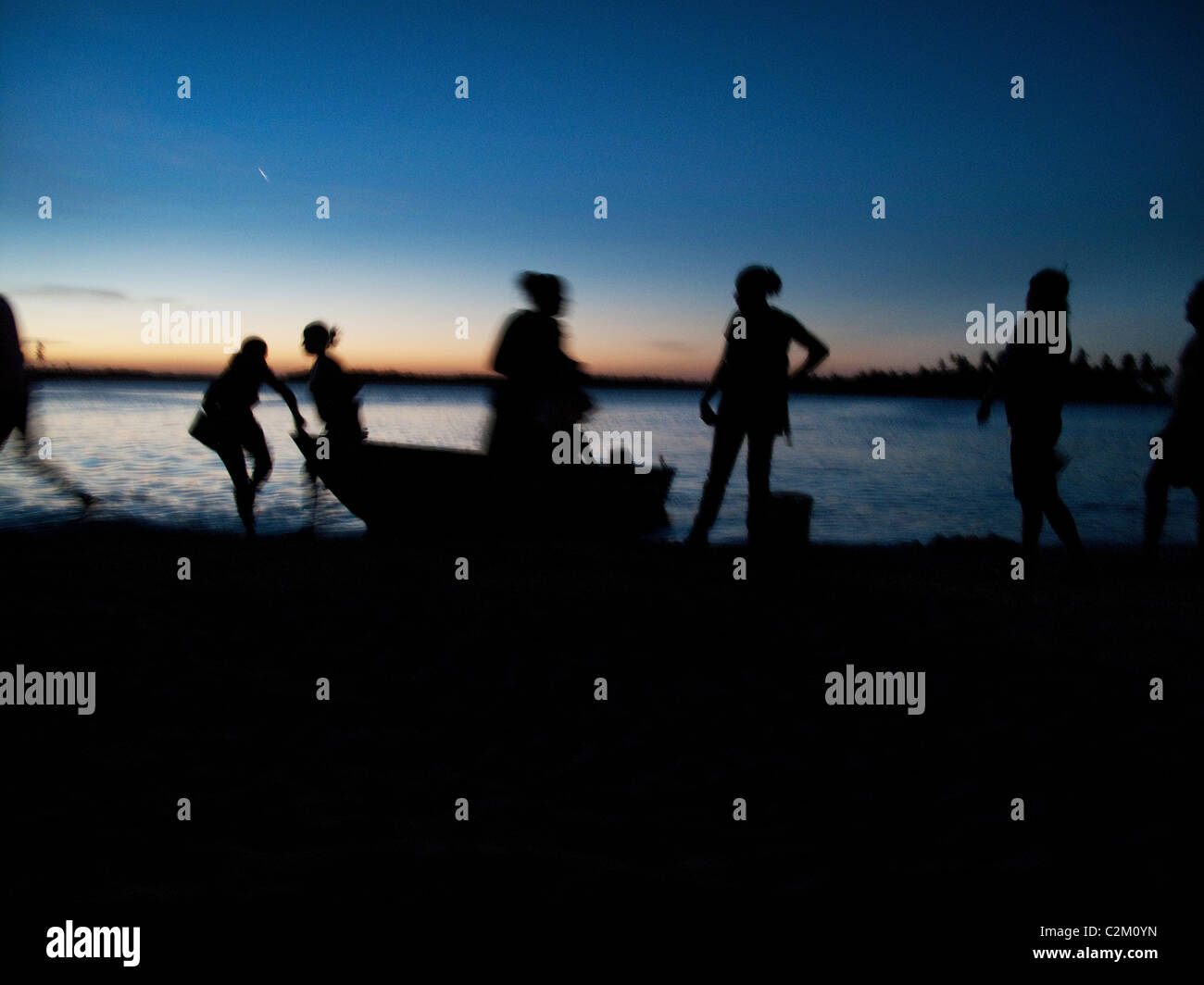 Group embarking from boat on beach at sunset, on Boipeba Island, Bahia, Brazil - Stock Image