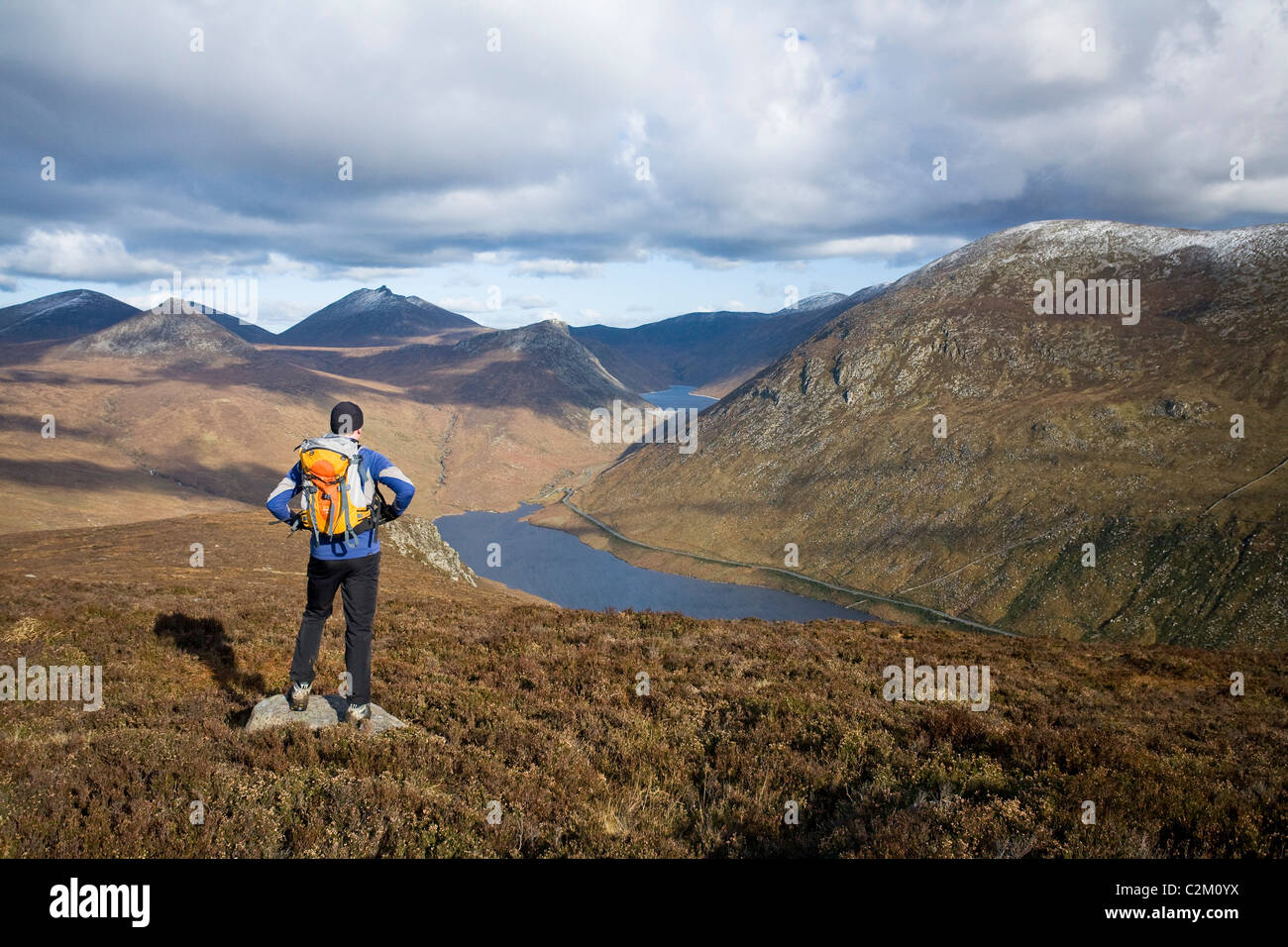 Walker looking along the Silent Valley from Slievenaglogh, Mourne Mountains, County Down, Northern Ireland. - Stock Image