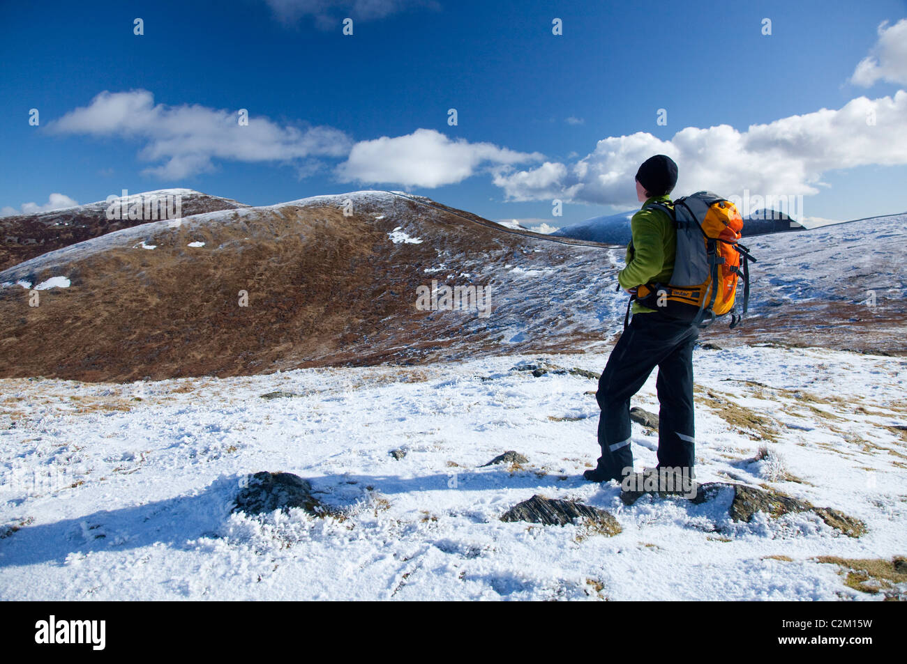 Winter walker near the summit of Ott Mountain, Mourne Mountains, County Down, Northern Ireland. - Stock Image