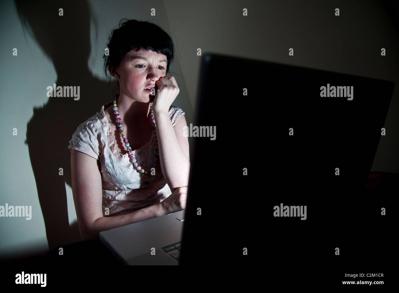 A young woman UK university student working on her laptop computer in bedroom at home, worried about email virus - Stock Image