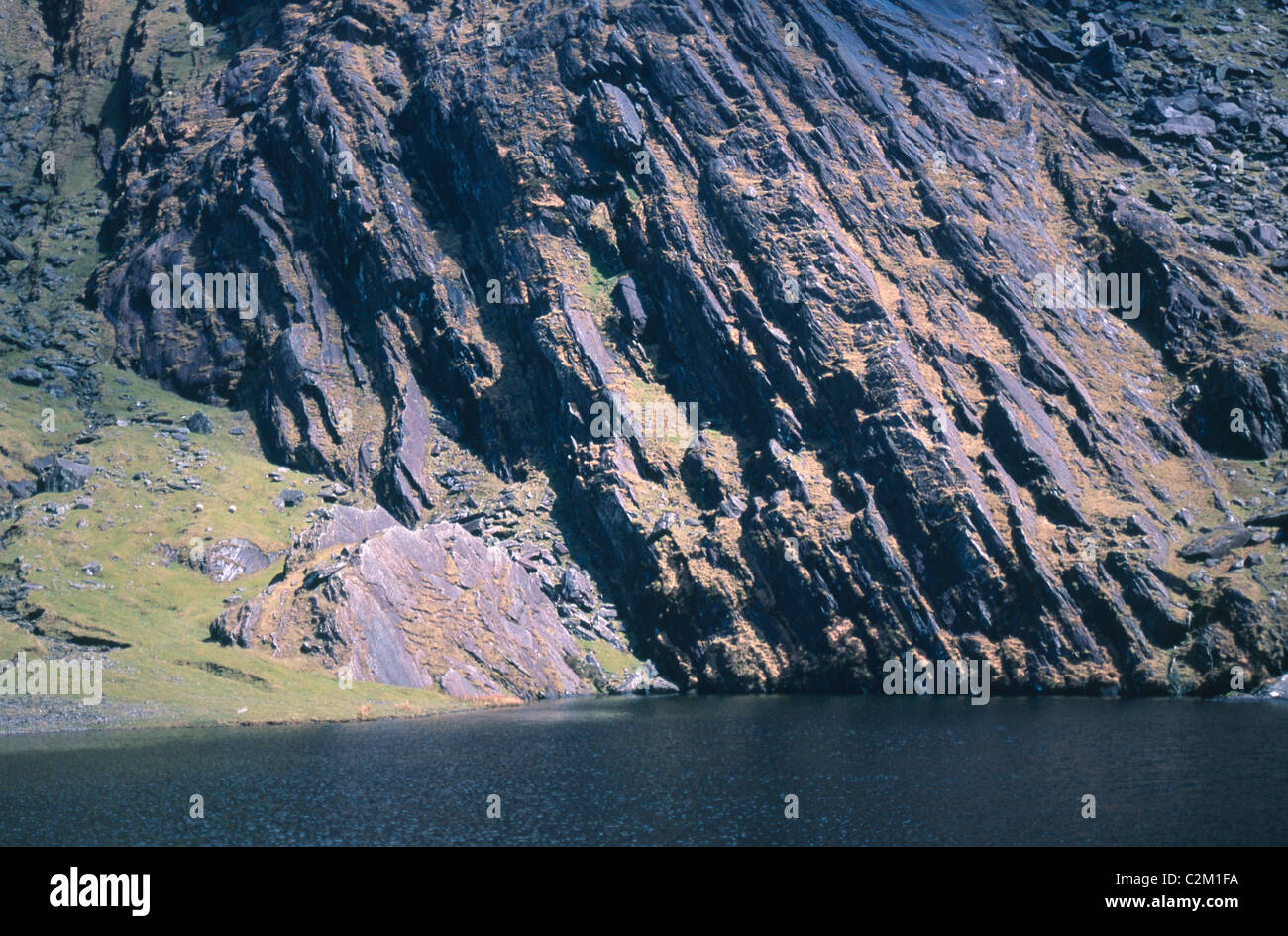 Folded sandstone rock beside a lake in Coomavoher, Knockmoyle Mountain, County Kerry, Ireland. - Stock Image
