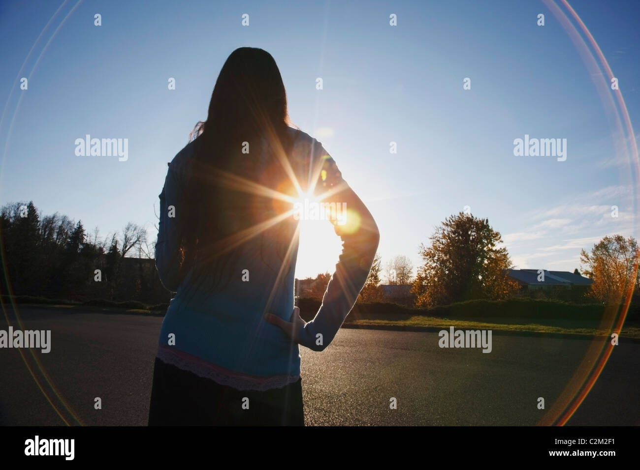 Beams Of Sunlight And A Circular Glare Around A Teenage Girl - Stock Image