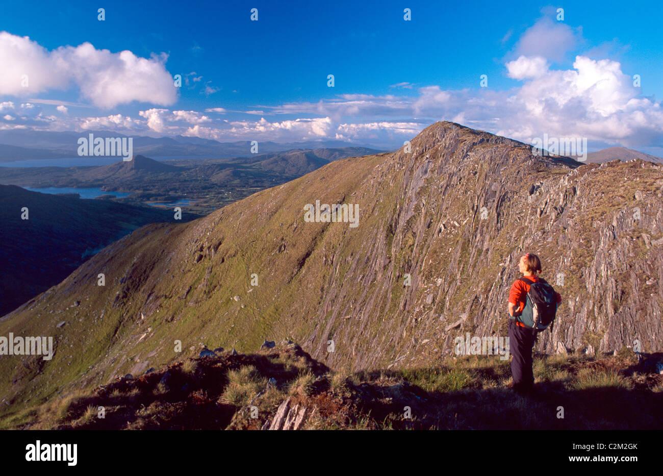 Walker looking towards Lackabane from Eskatarriff Mountain, Beara Peninsula, County Kerry, Ireland. - Stock Image