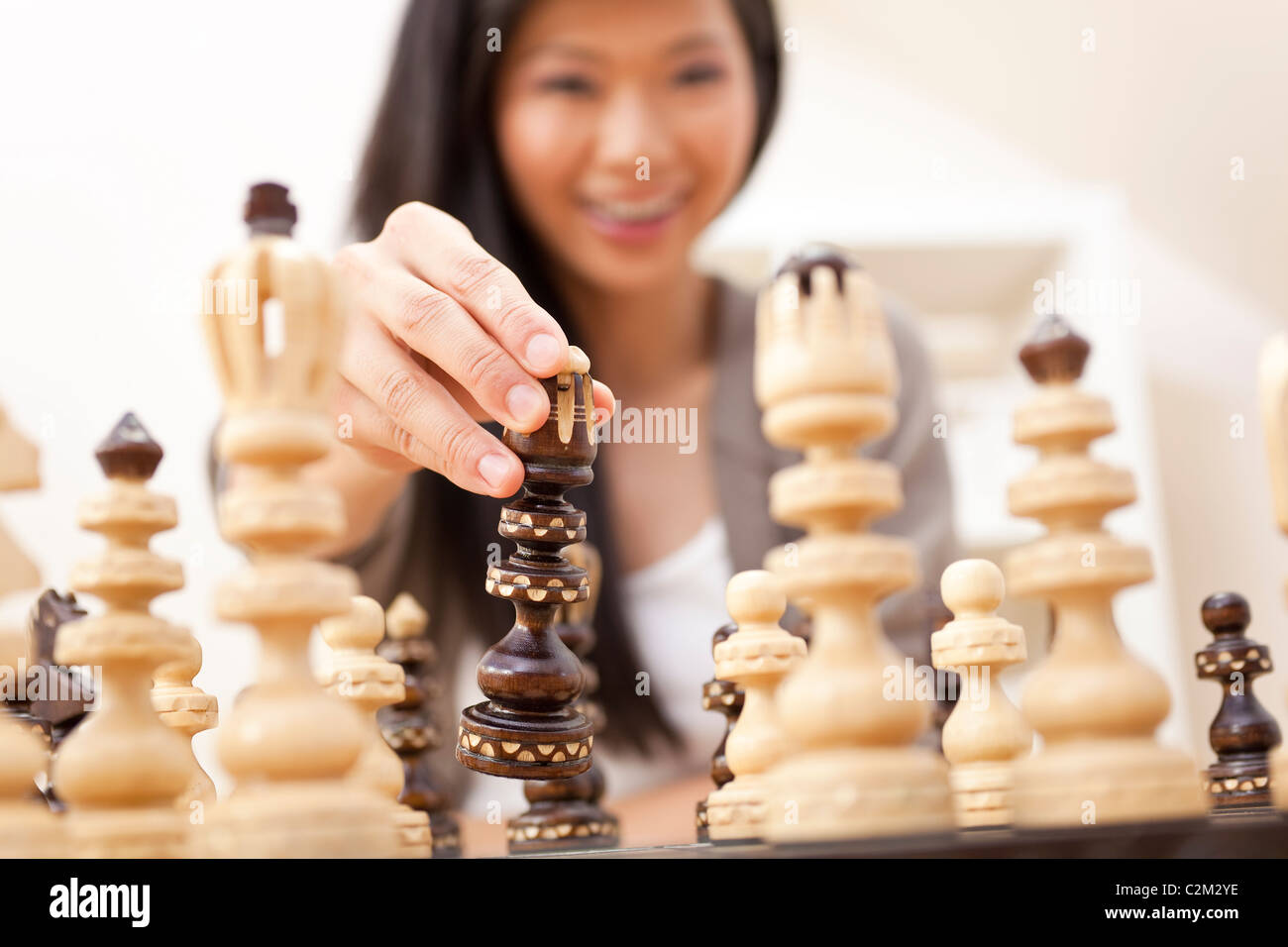 Selective focus photograph of beautiful young Chinese Asian Oriental woman playing chess - Stock Image