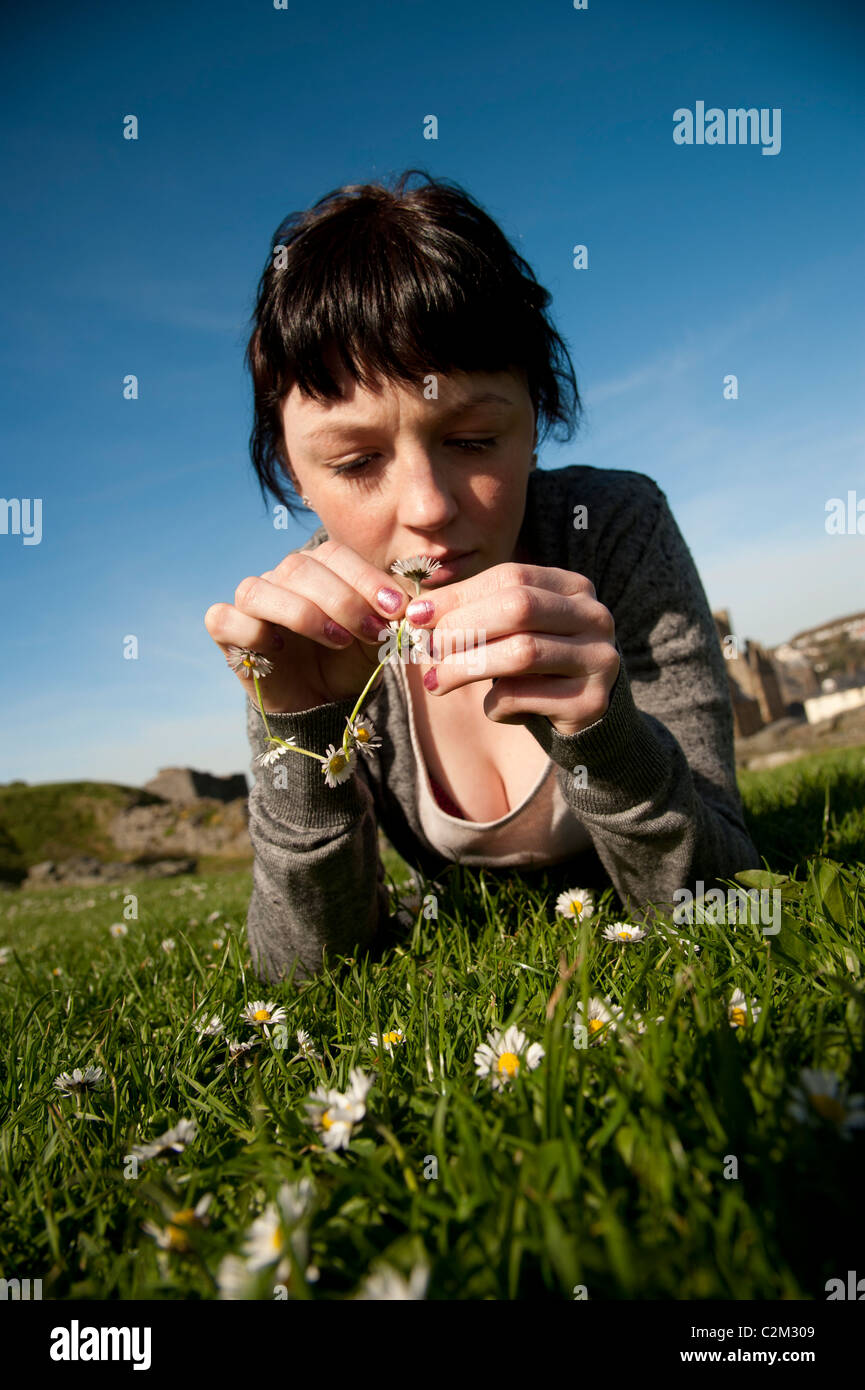 A young woman making daisy chains UK - Stock Image
