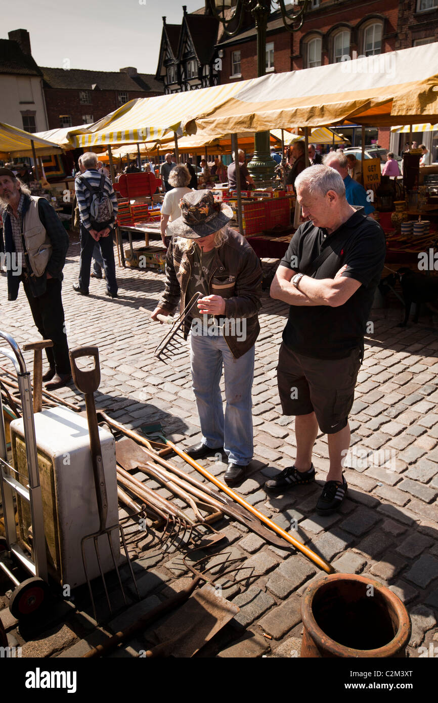 UK, England, Staffordshire, Leek, Market Place, antiques and collectibles market, man inspecting old garden rake - Stock Image