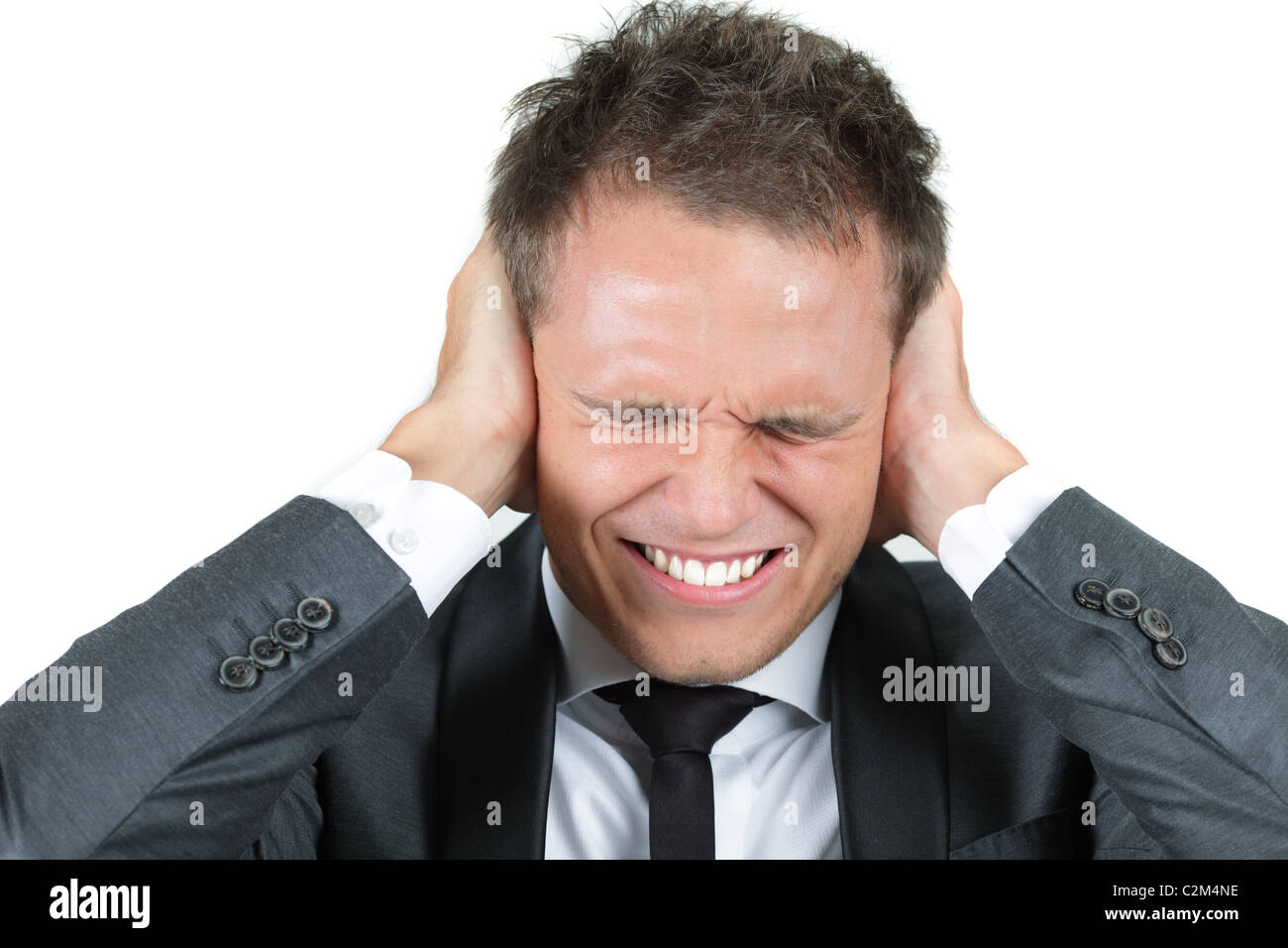 Young man, holding hands on his ears, protecting himself from noise - Stock Image