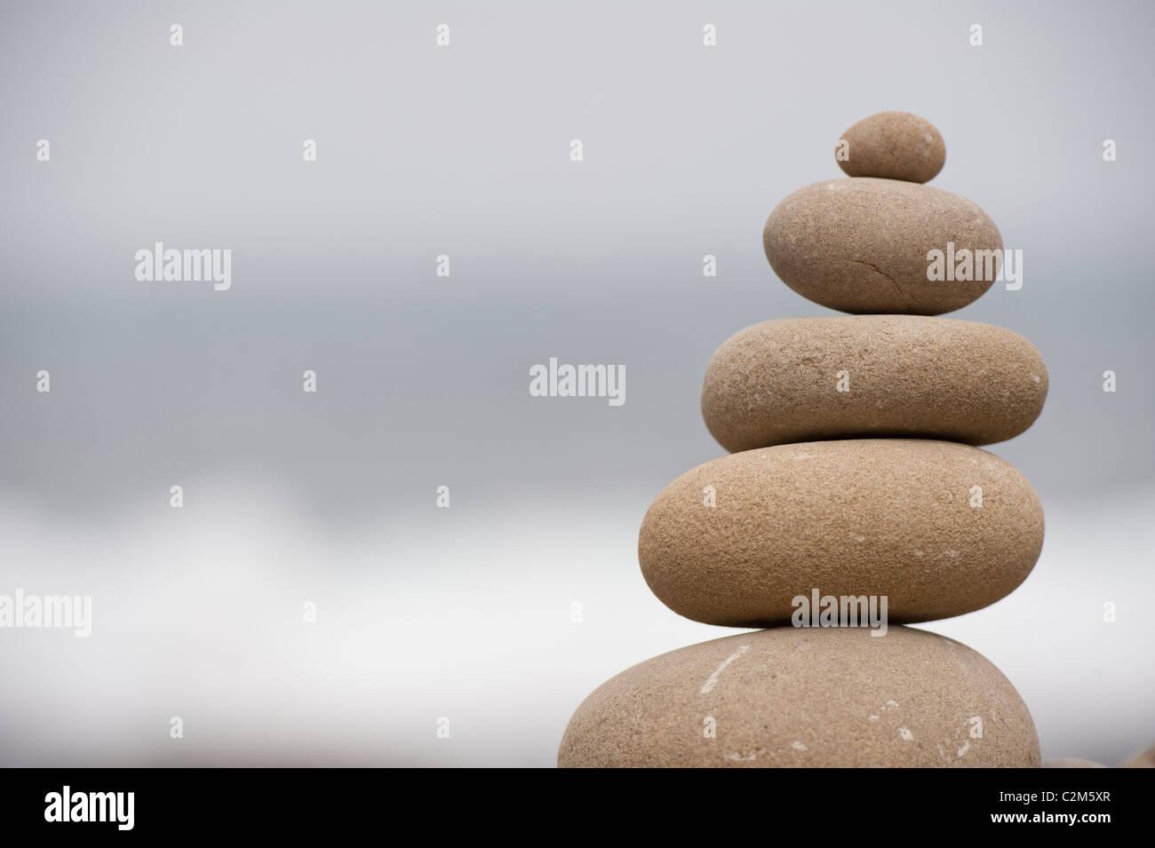 pile of balanced rocks against ocean background - Stock Image