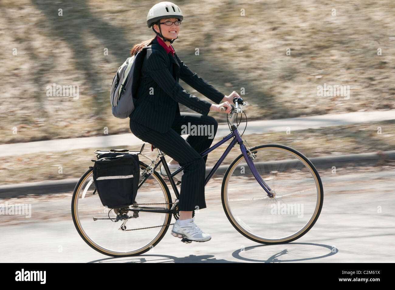 Pretty Asian businesswoman bicycling to work - Stock Image