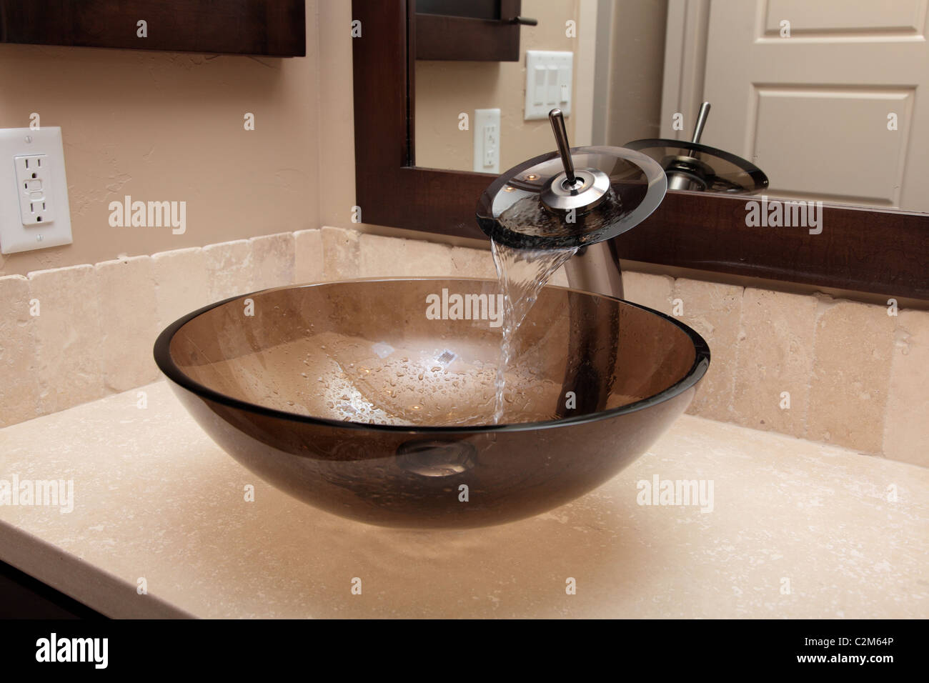 Brown Glass Bowl Sink With Water Falling From The Faucet