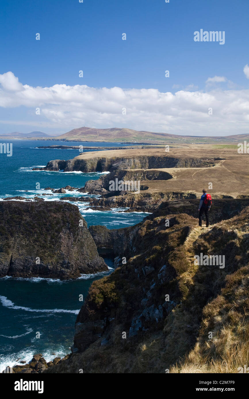 Coastal walker looking over the cliifs near  Erris Head, Belmullet Peninsula, County Mayo, Ireland. - Stock Image