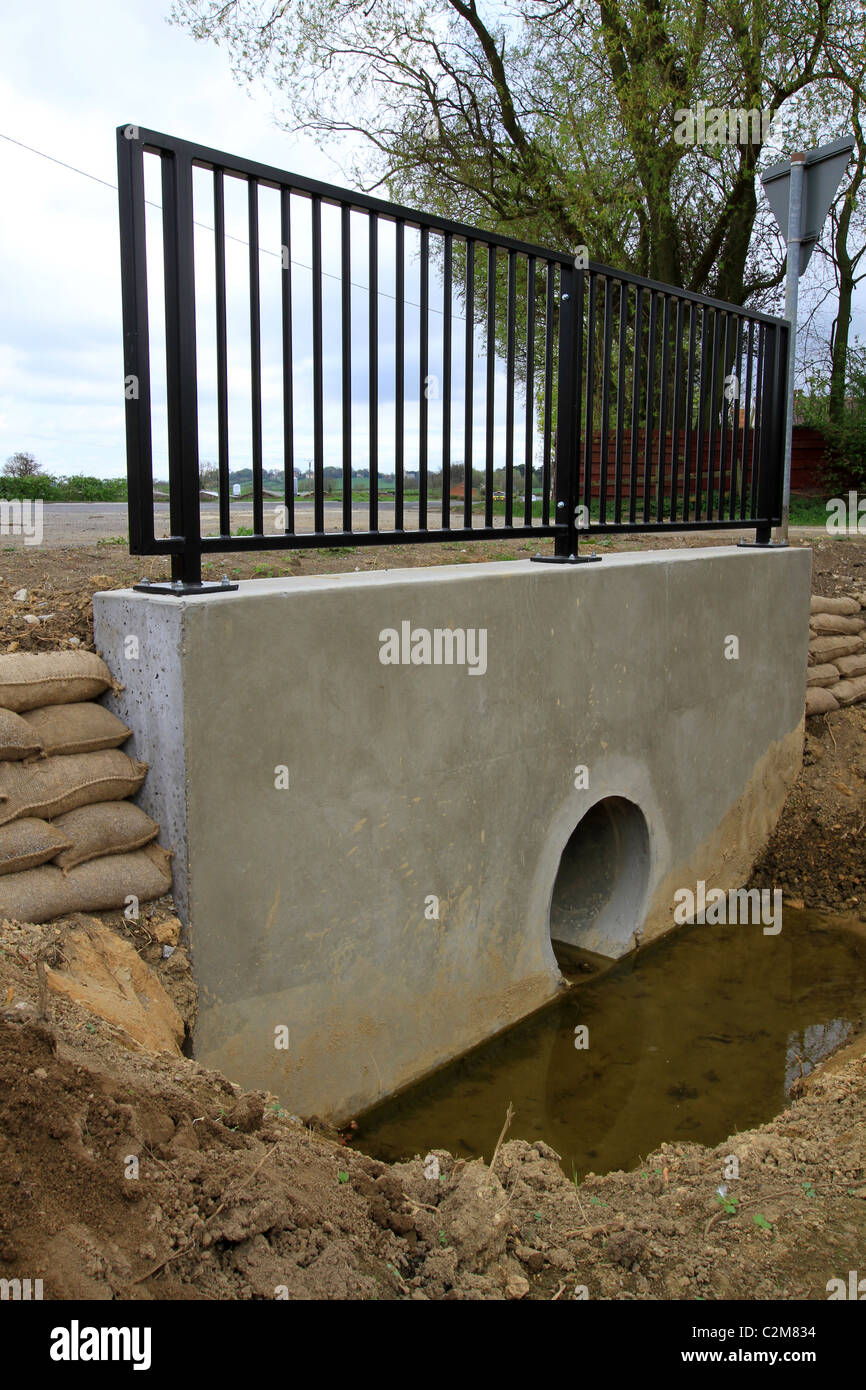 A culvert is a device used to channel water. It may be used to allow water to pass underneath a road, railway, or - Stock Image