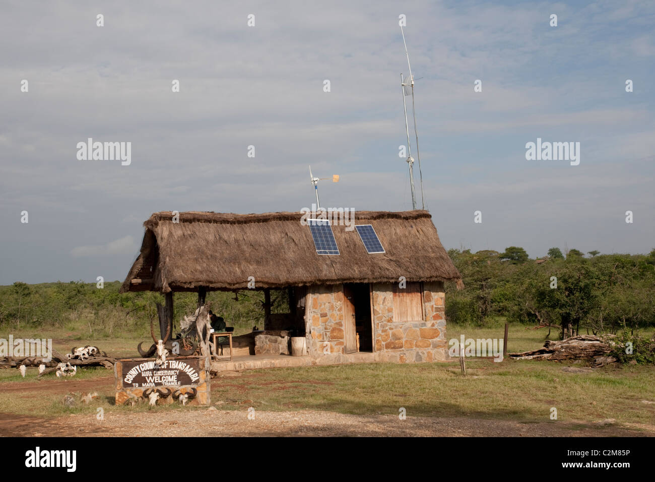 Solar PV panels & wind turbine on thatched roof game reserve entrance Masai Mara Kenya Stock Photo