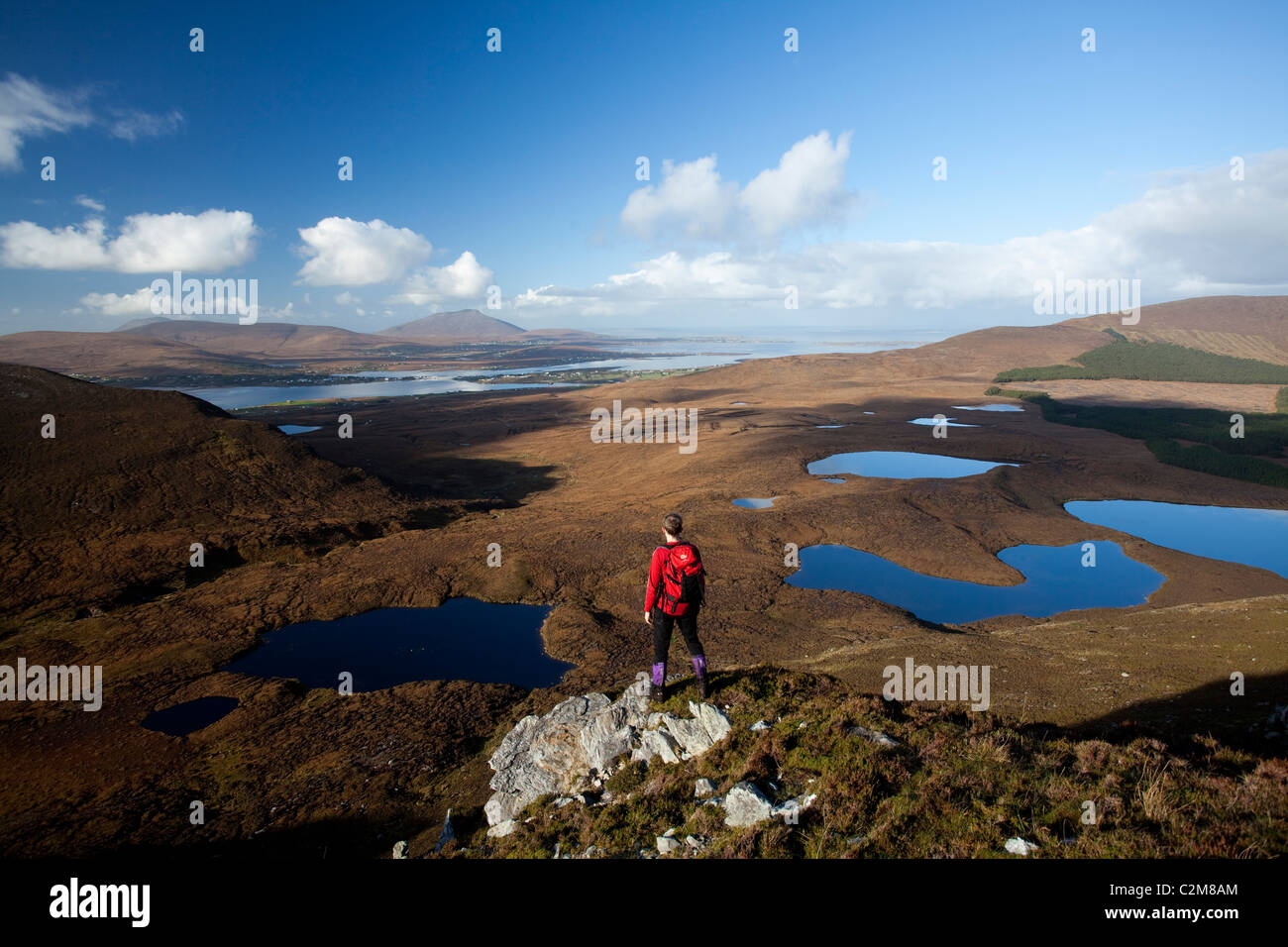 Walker looking towards Achill Island from Corraun Hill, County Mayo, Ireland. - Stock Image