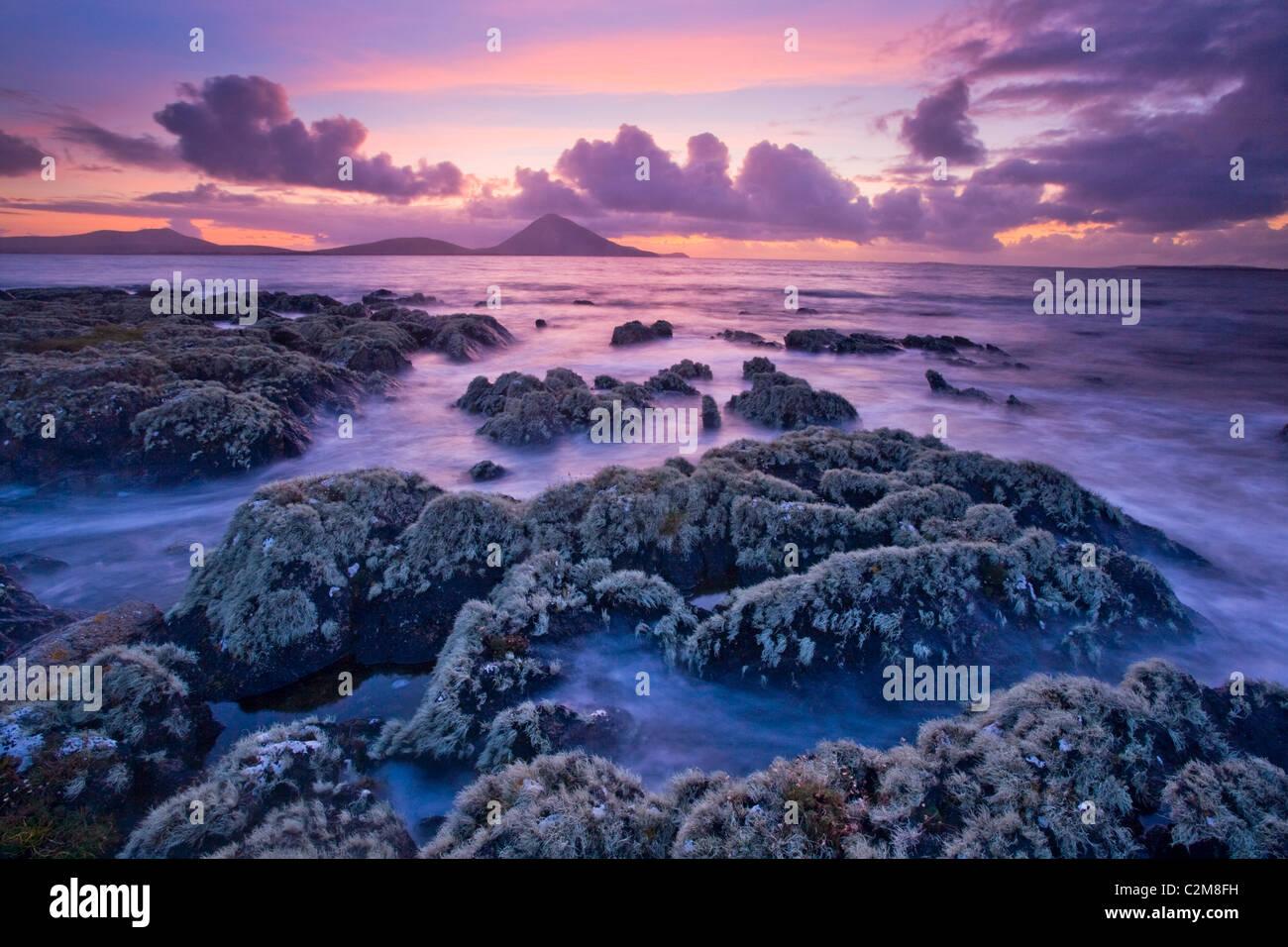 Lichen-covered shoreline at sunset, Ballycroy, County Mayo, Ireland. - Stock Image