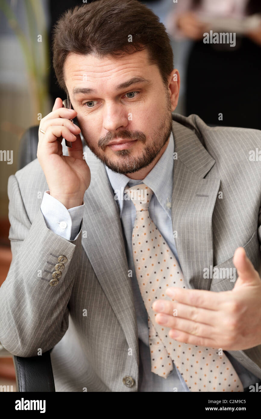 Portrait of a mature business man screaming in his cellphone in office environment - Stock Image
