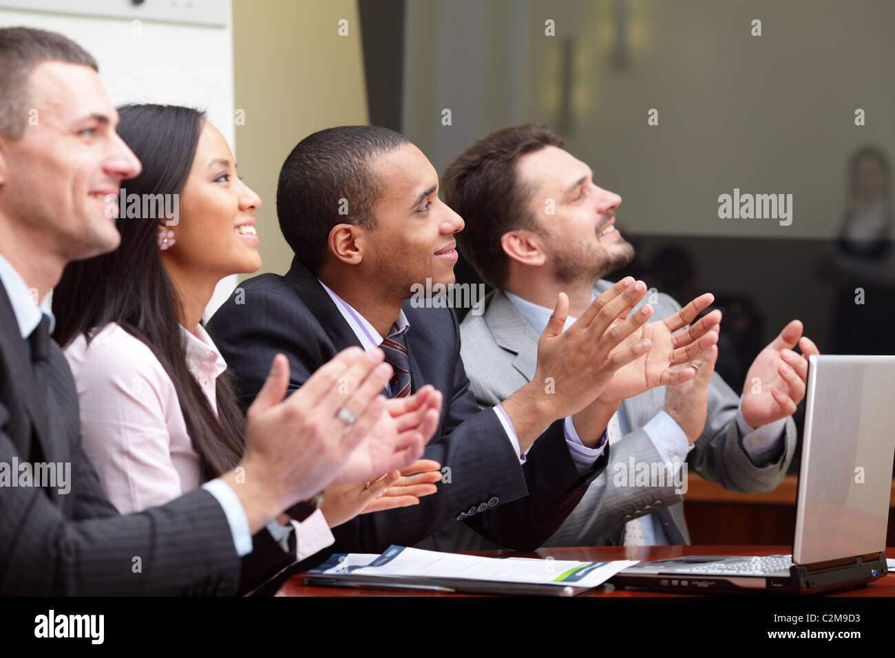 Multi ethnic business group greets somebody with clapping and smiling. Focus on african-american man - Stock Image