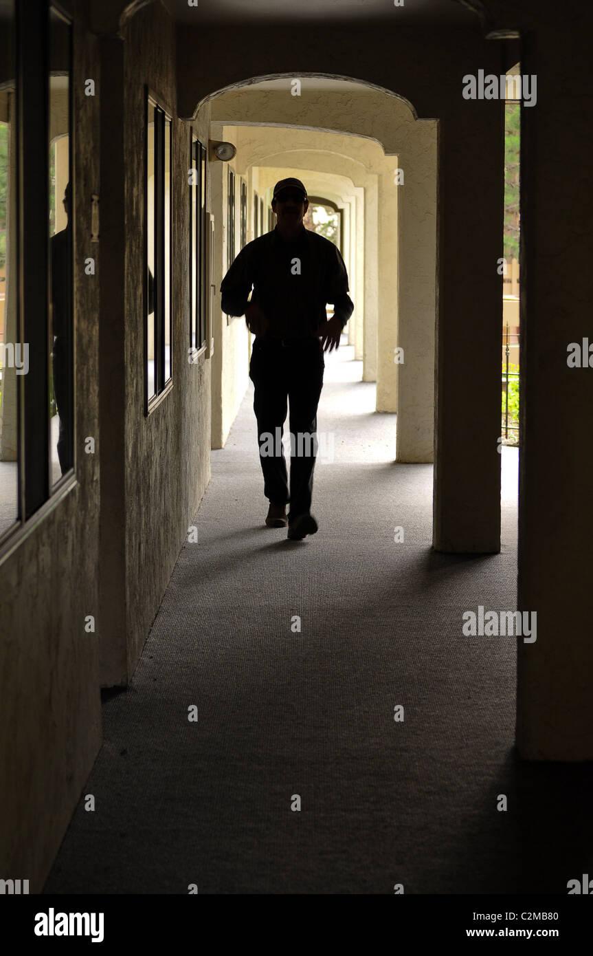 Man walking down coridoor - Stock Image