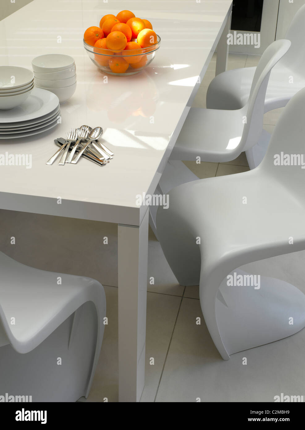 House in Chelsea, London. Modern white dining table with cantilevered white moulded chairs and white floor - Stock Image