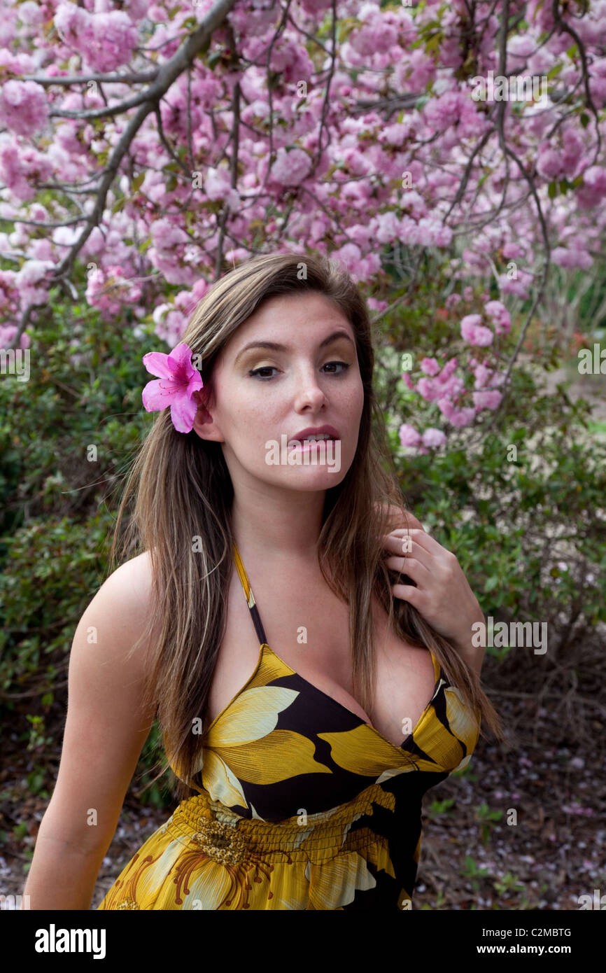 Pretty woman in yellow dress outside with purple flowers from a tree pretty woman in yellow dress outside with purple flowers from a tree and looking at the viewer mightylinksfo
