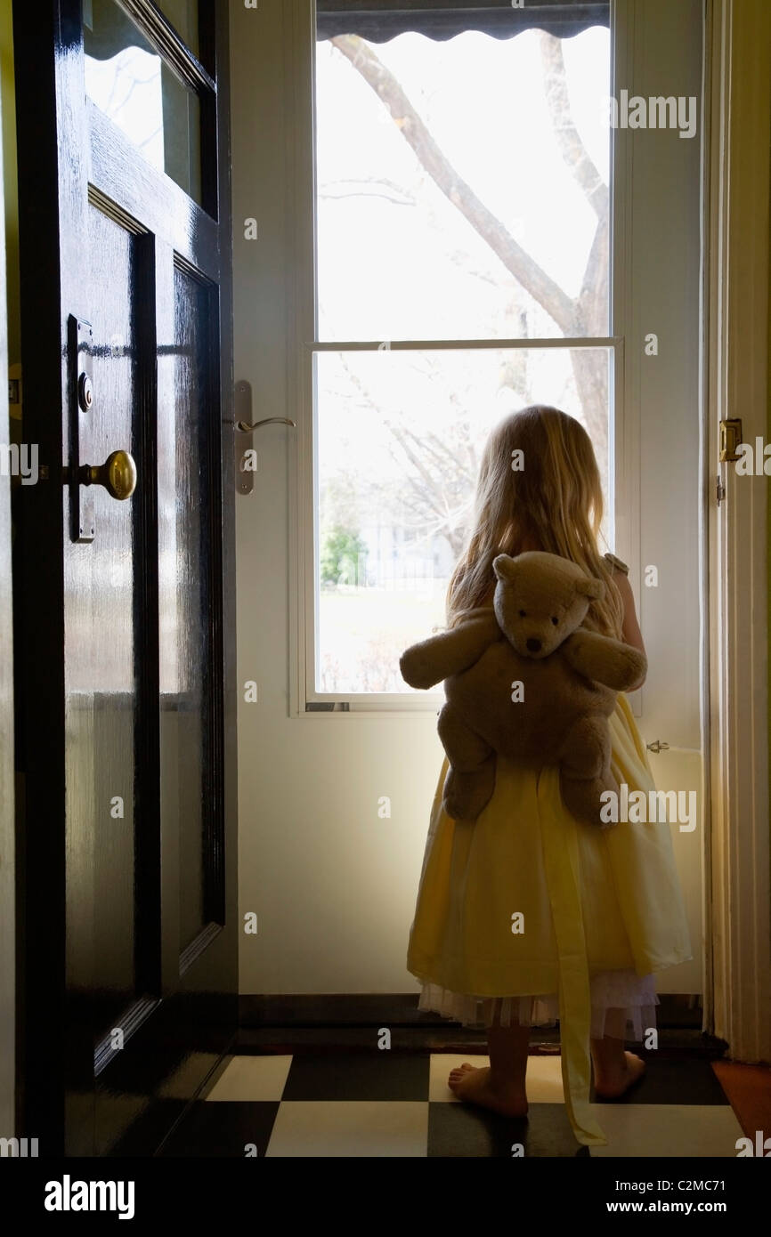 A Girl With A Teddy Bear Backpack Looking Out The Door & A Girl With A Teddy Bear Backpack Looking Out The Door Stock Photo ...