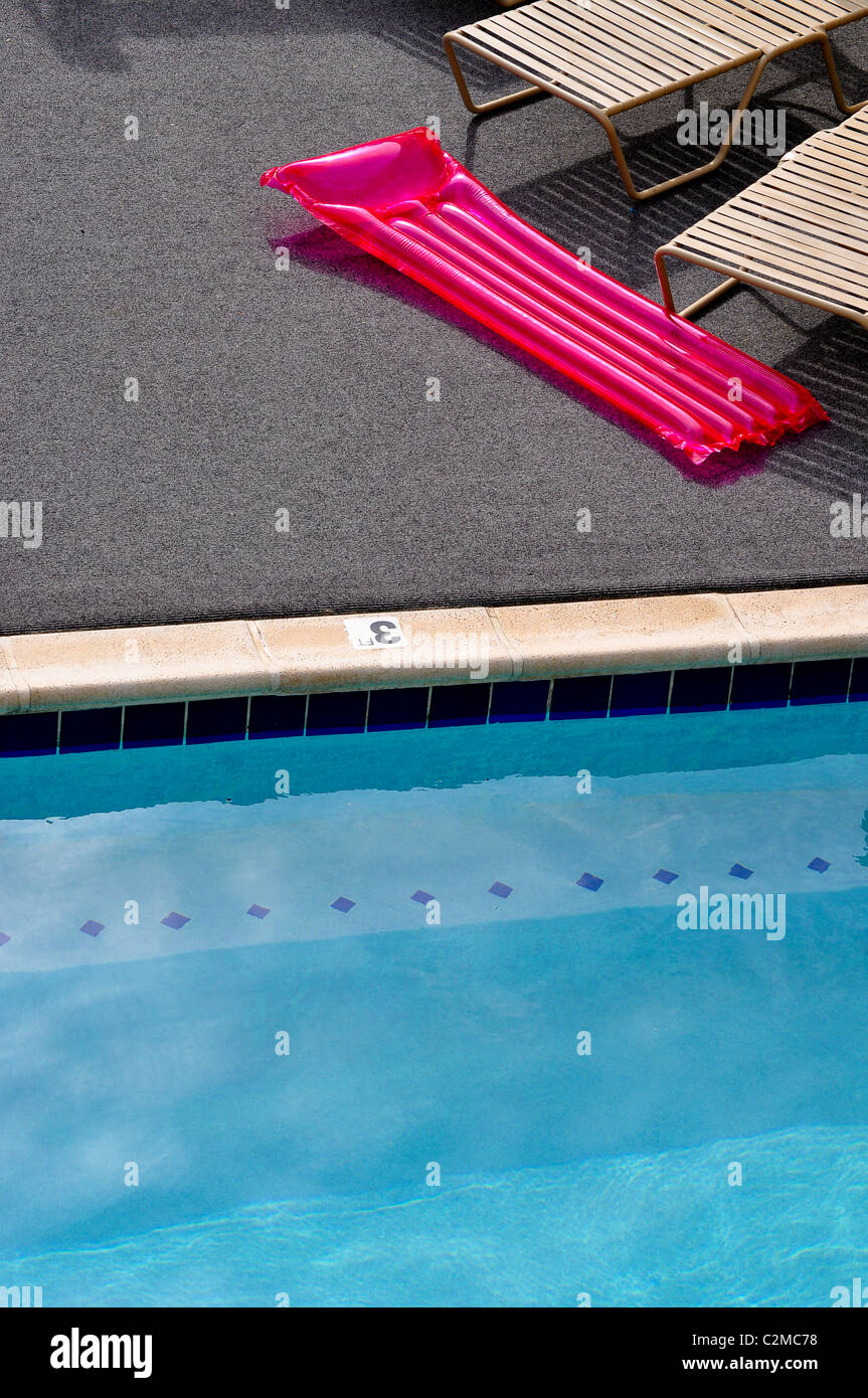 Swimming pool and inflatable raft - Stock Image