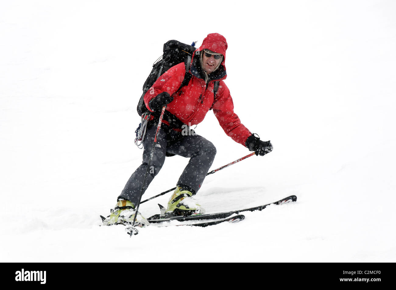 A skier descending a short steep slope, in poor visibility, whilst skiing the Haute Route - Stock Image