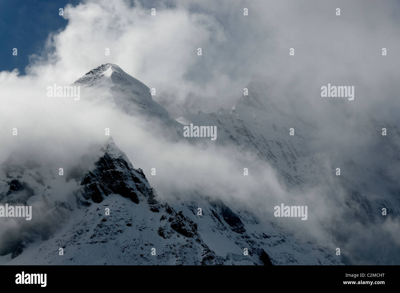Grand Combin appearing from clearing storm clouds in the Central Valais part of the Swiss Alps. - Stock Image